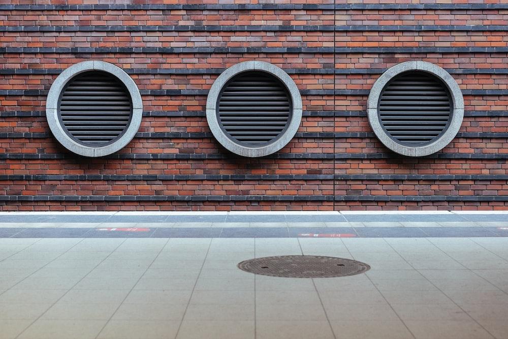 three round black tunnel on brown concrete brick building at daytime
