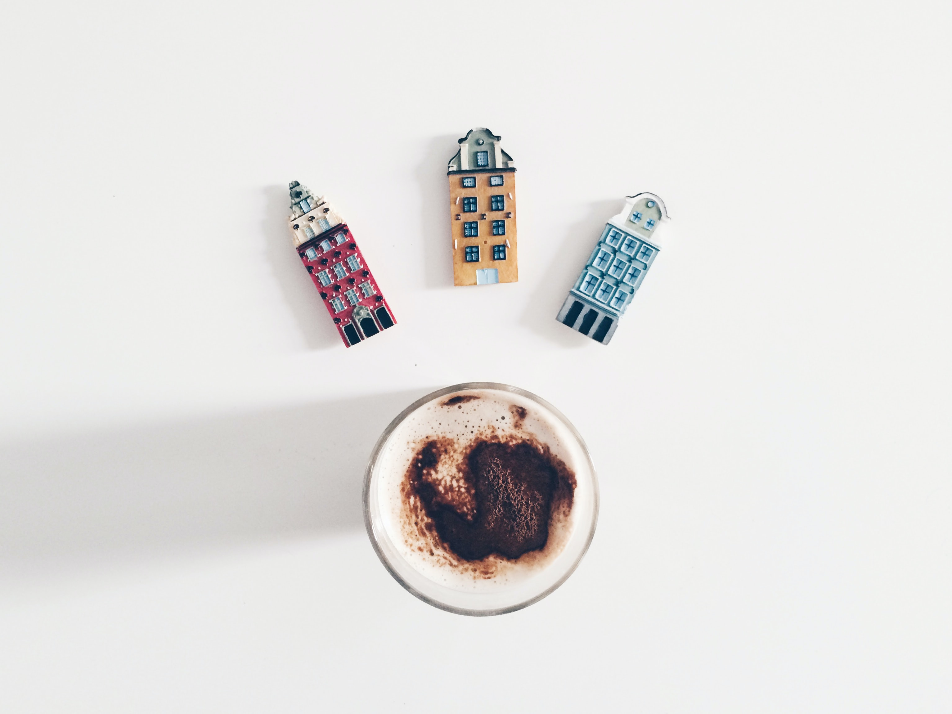 Cappuccino in a clear glass with three magnets in the shape of buildings above the glass