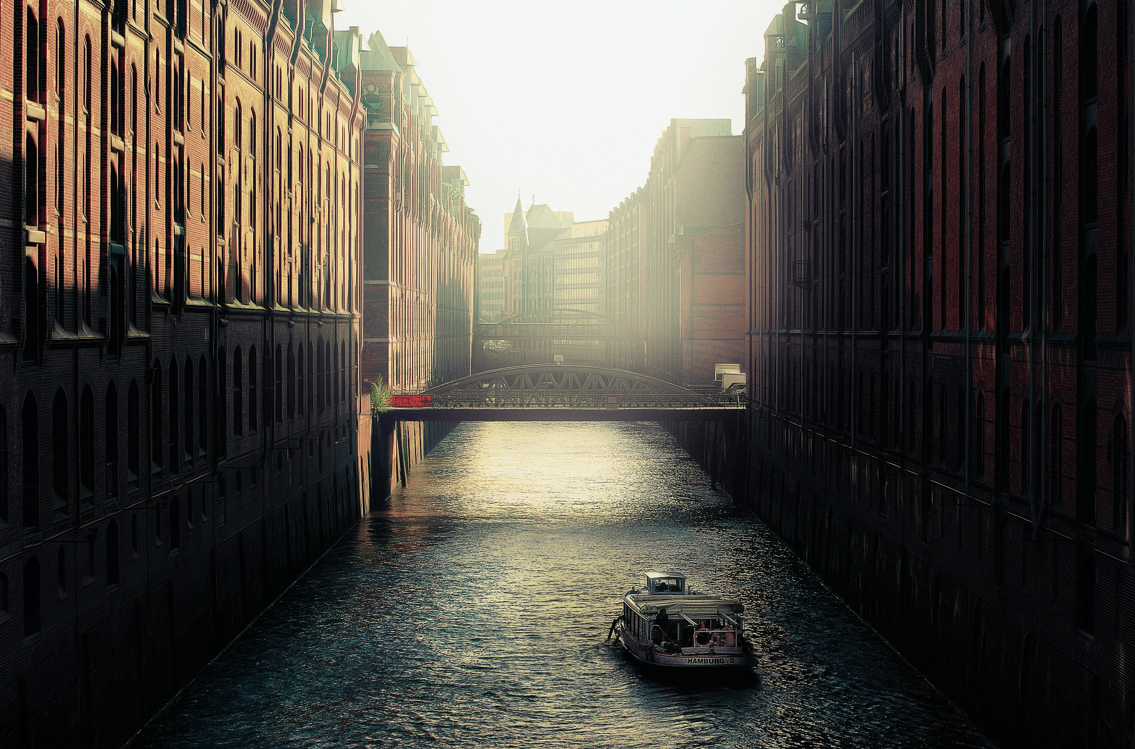 Boat rides down the canal lined with bridges in Speicherstadt