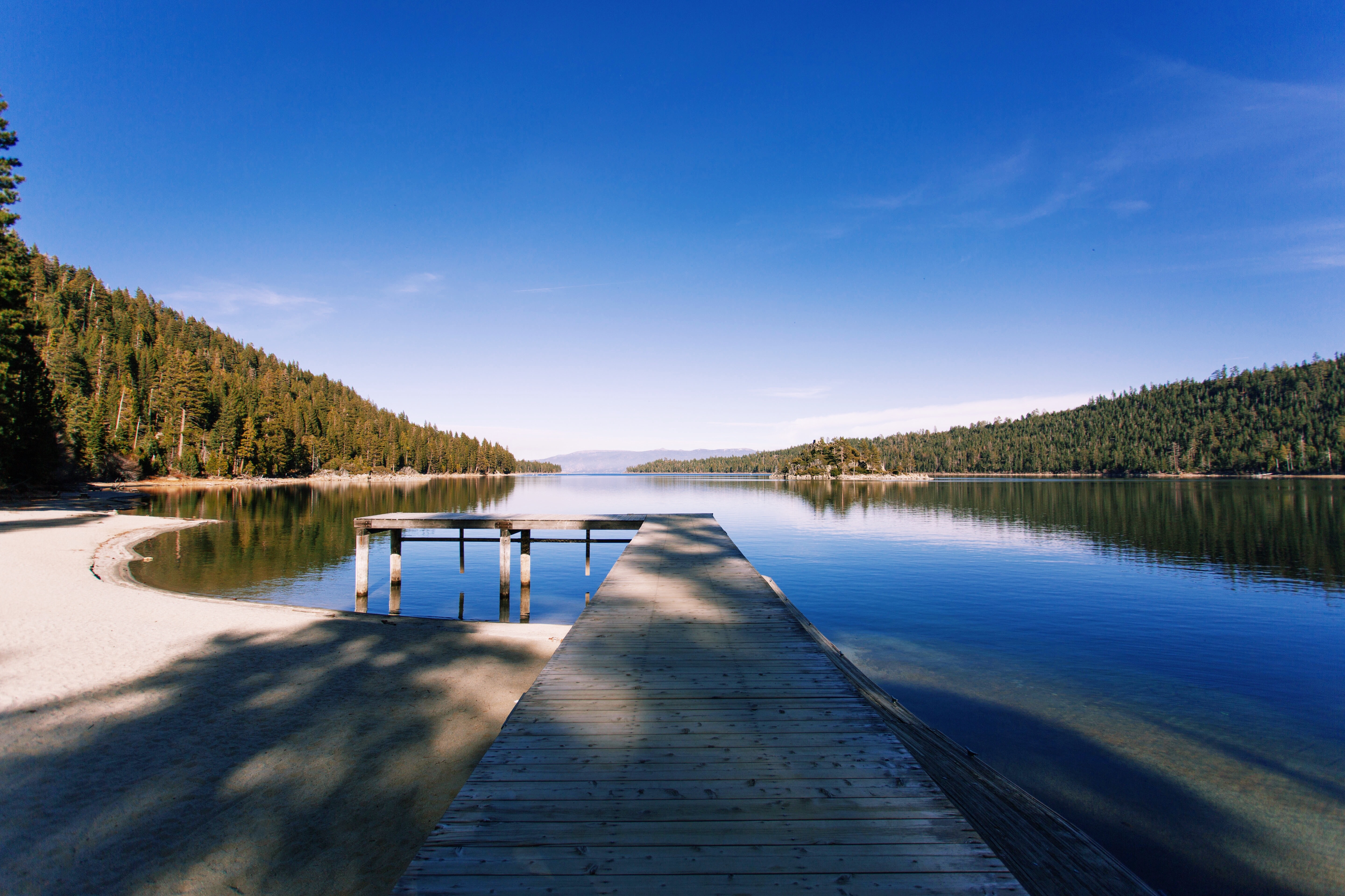 A pier on a lake next to a small sandy beach