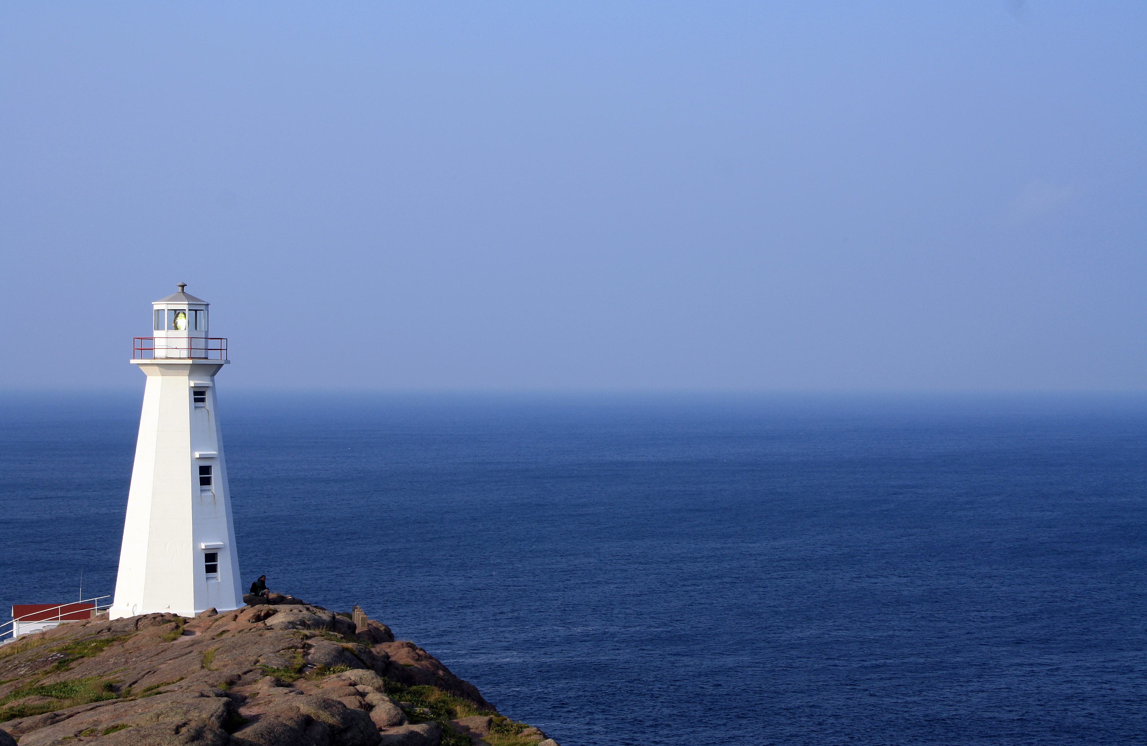 white lighthouse facing calm sea