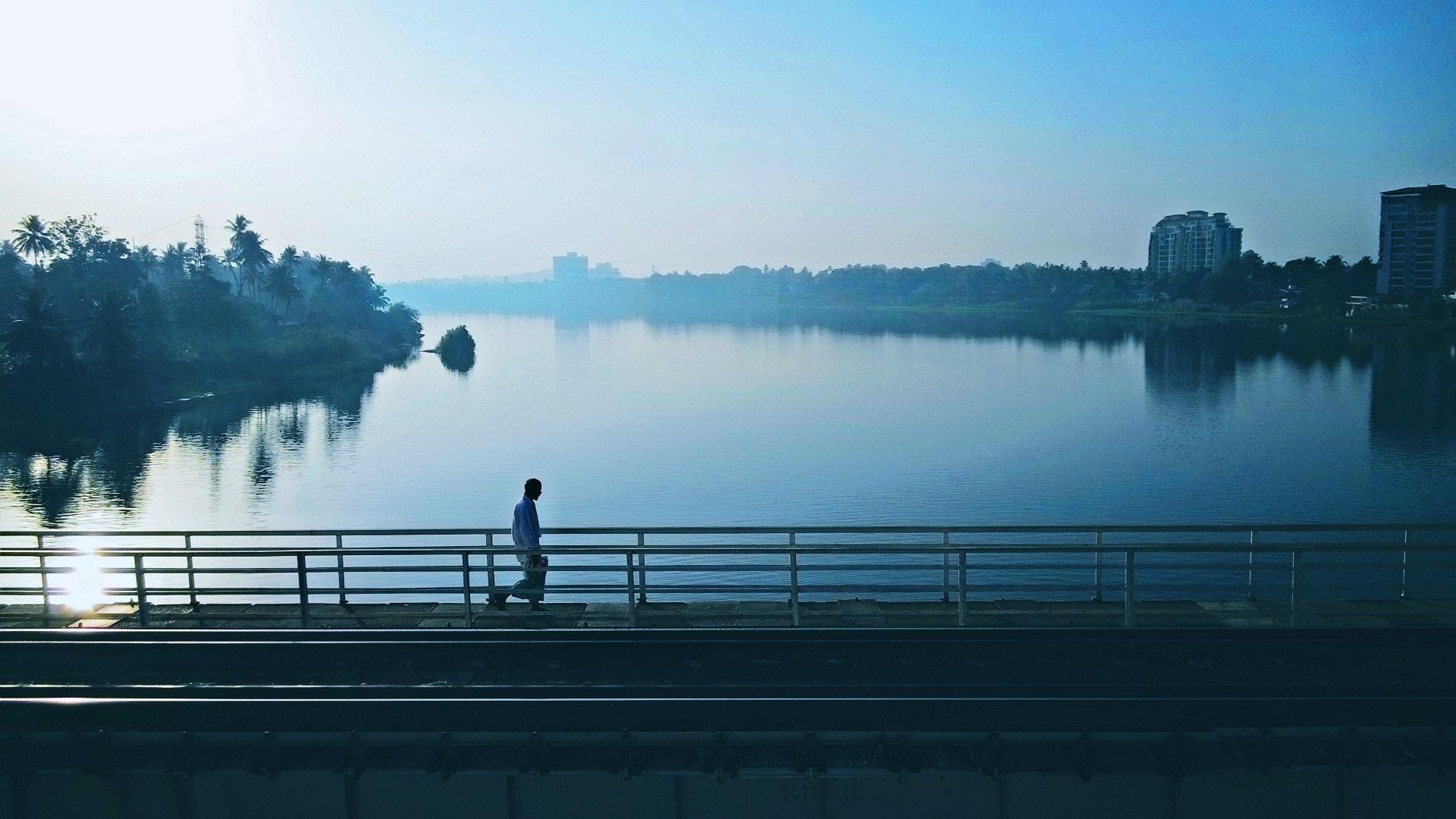 person walking on bridge near body of water
