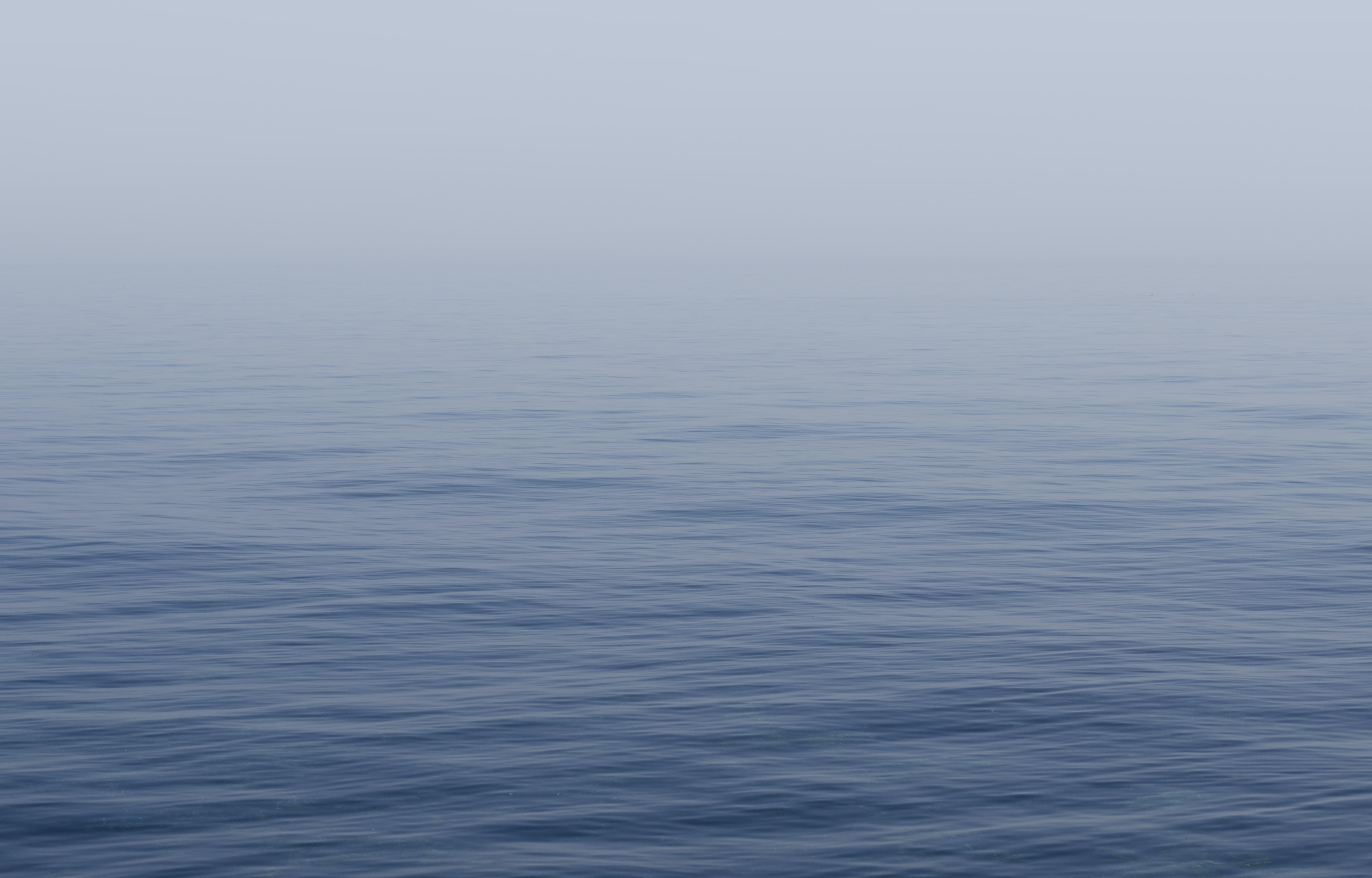 Calm, blue sea covered in a soft mist