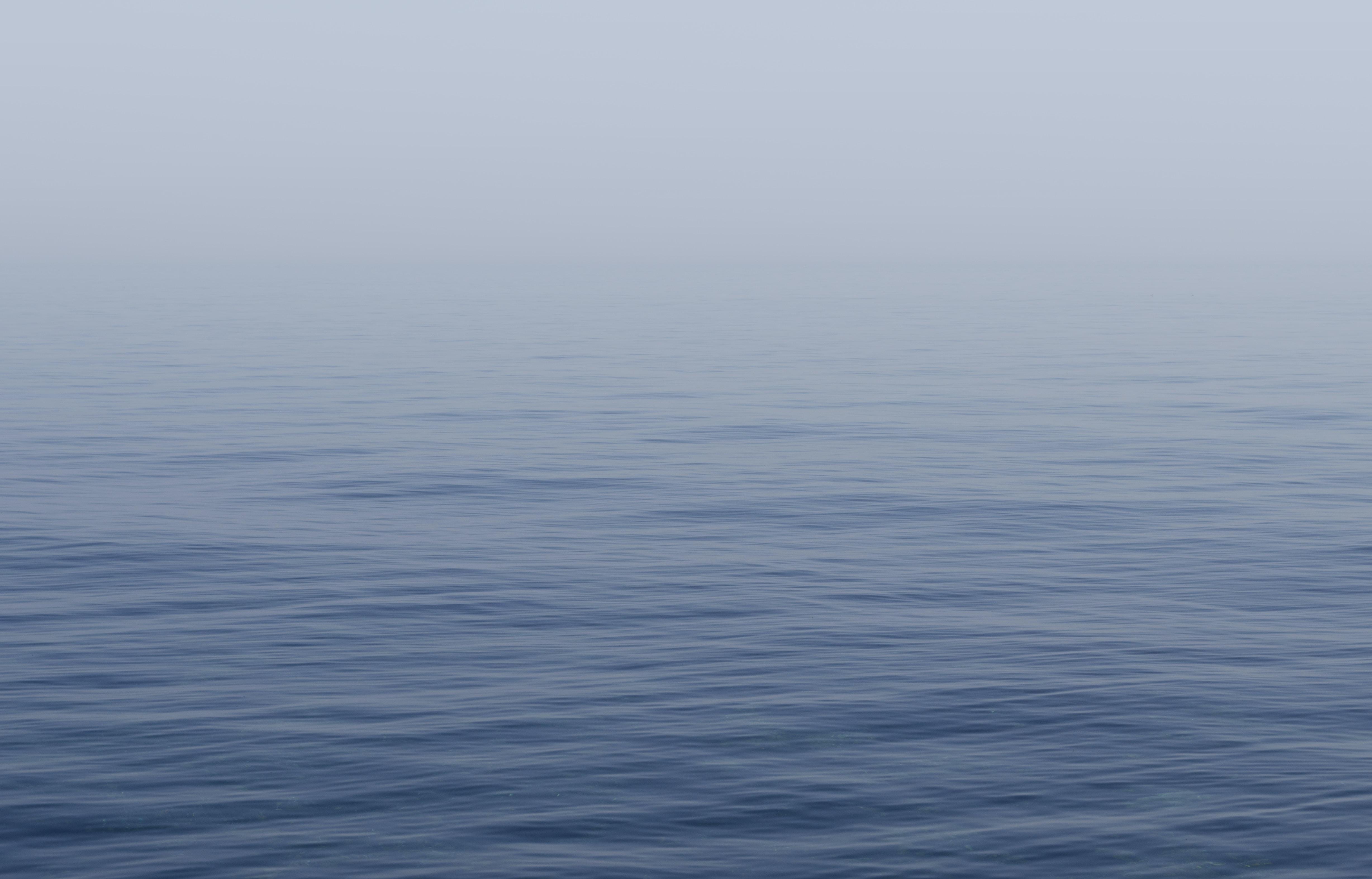 Calm, blue sea covered in a soft mist