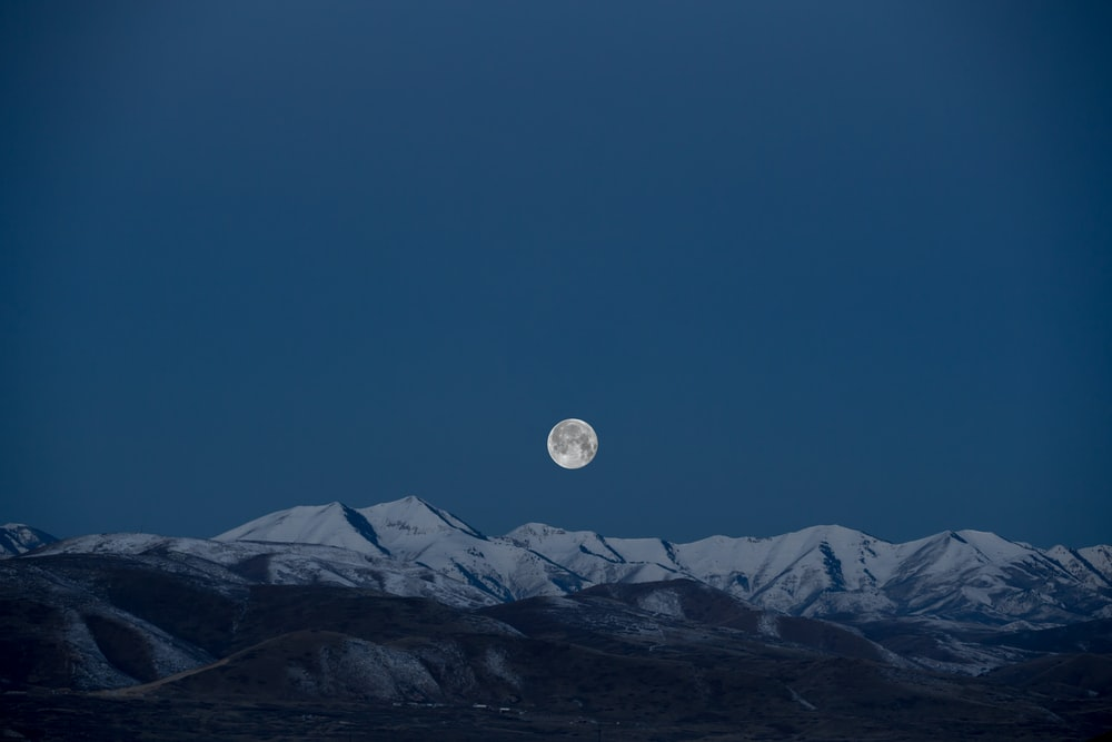 full-moon above snow-capped mountain painting