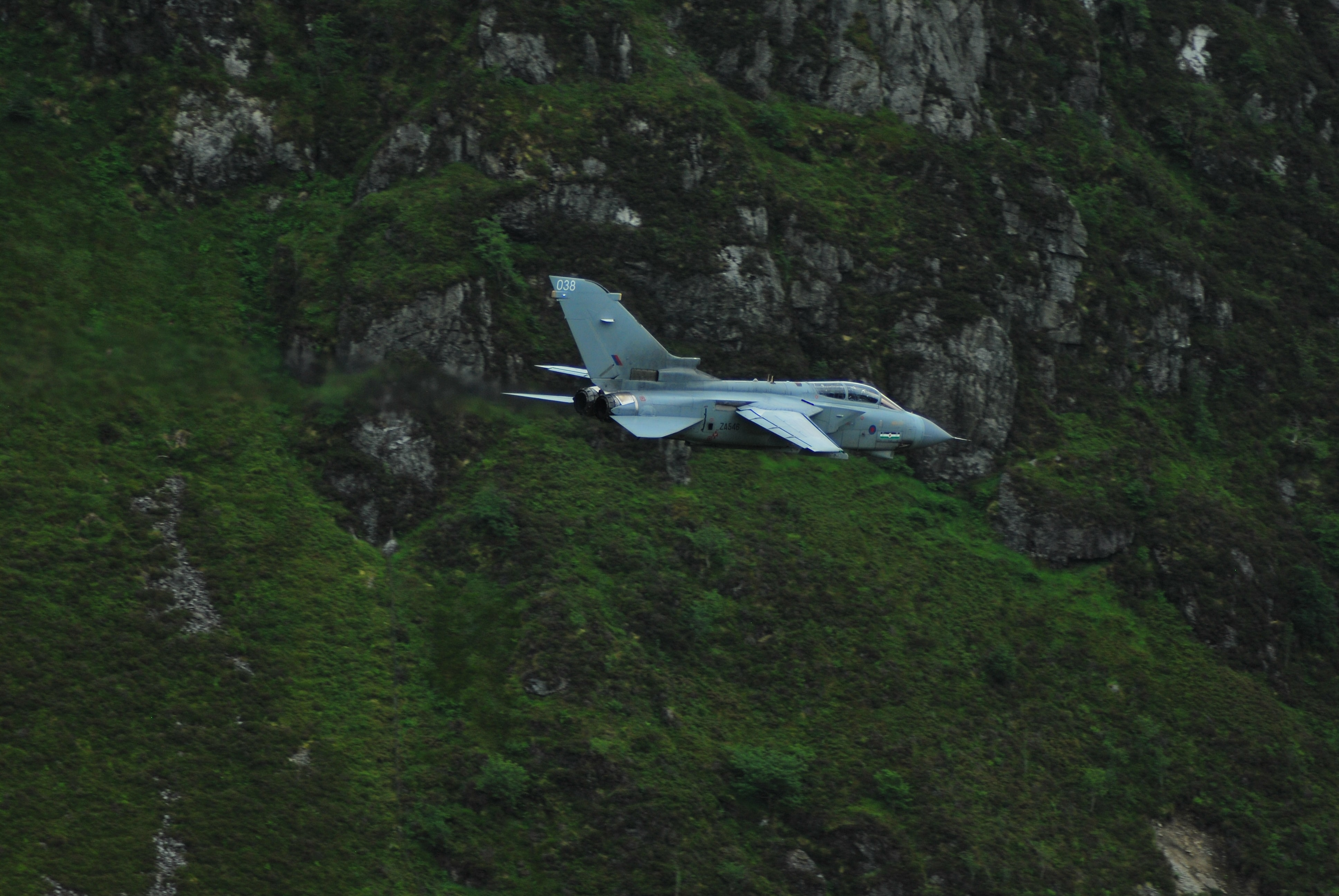 A small plane flies in front of a green mossy mountain