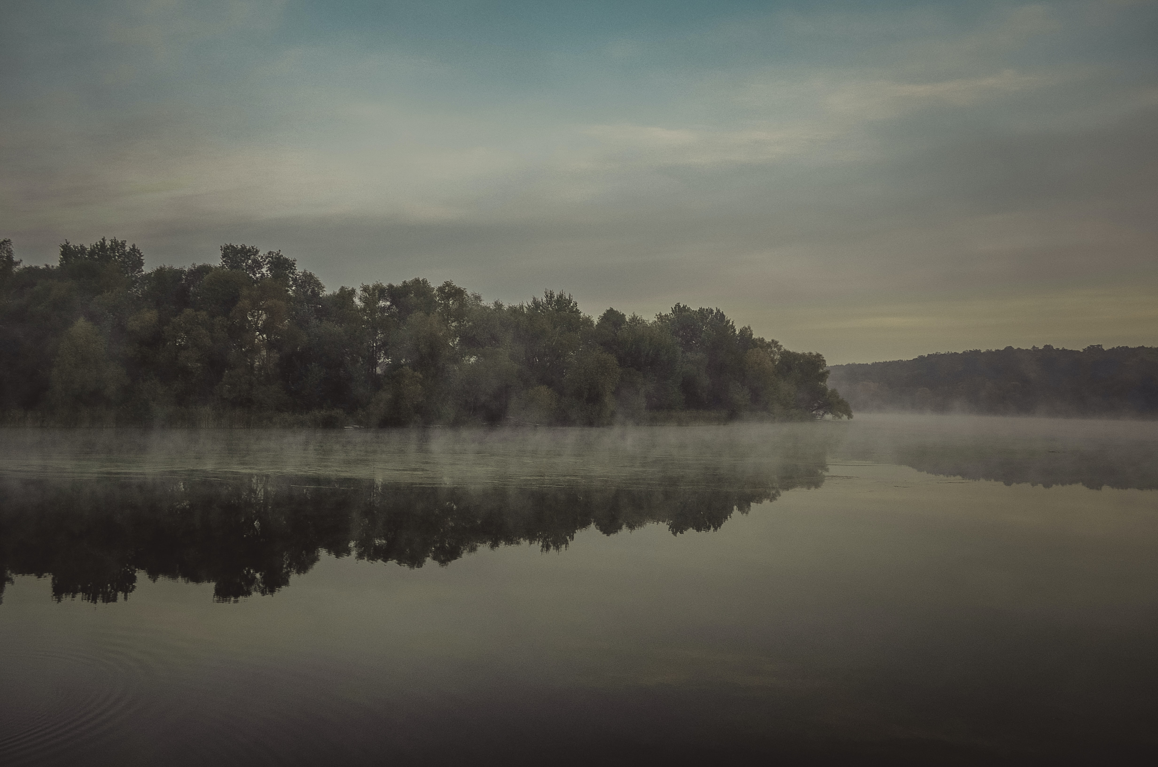 A patchy fog over the surface of a lake in the evening