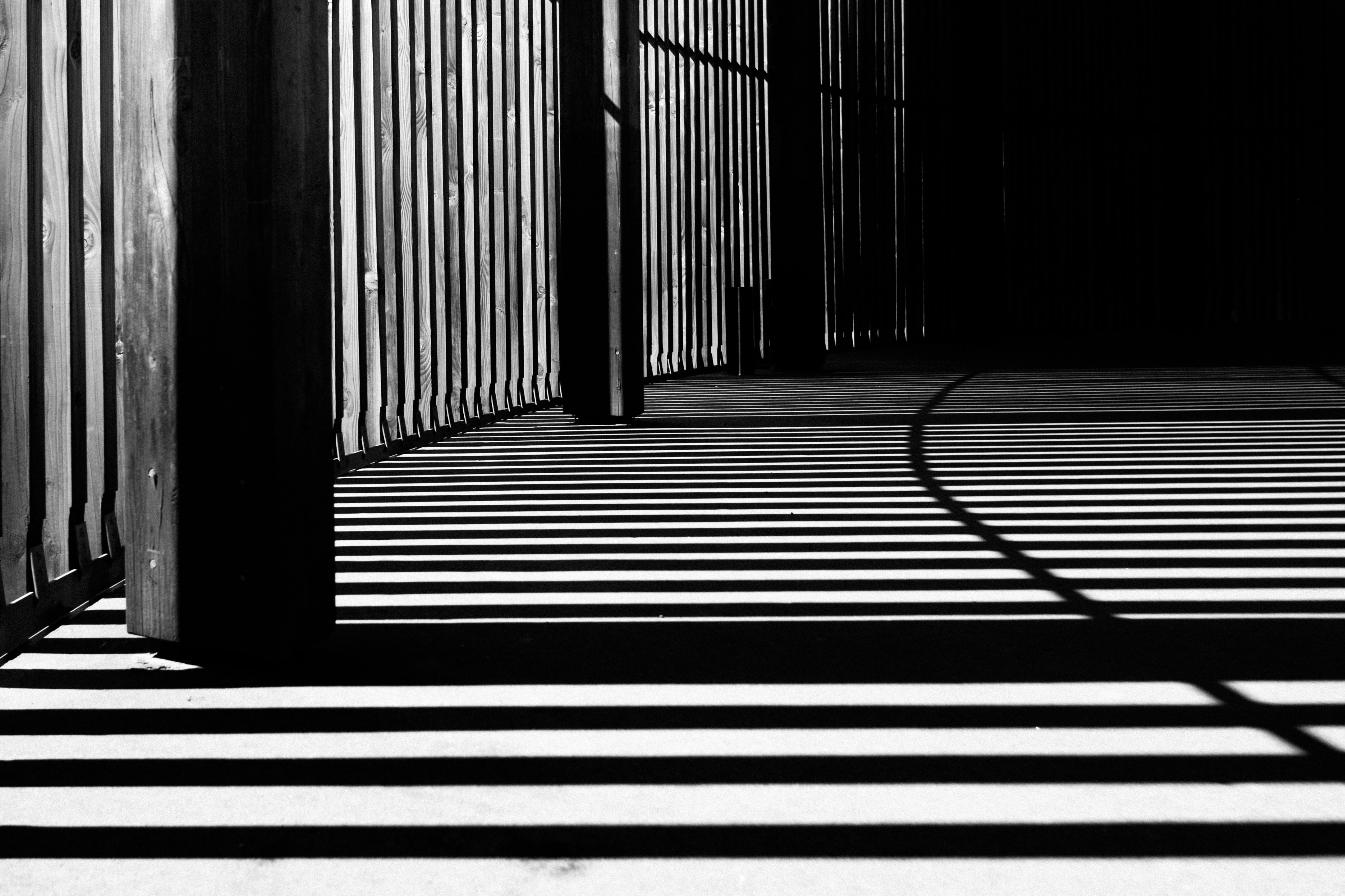 The shadows from a building structure creating lines across the floor