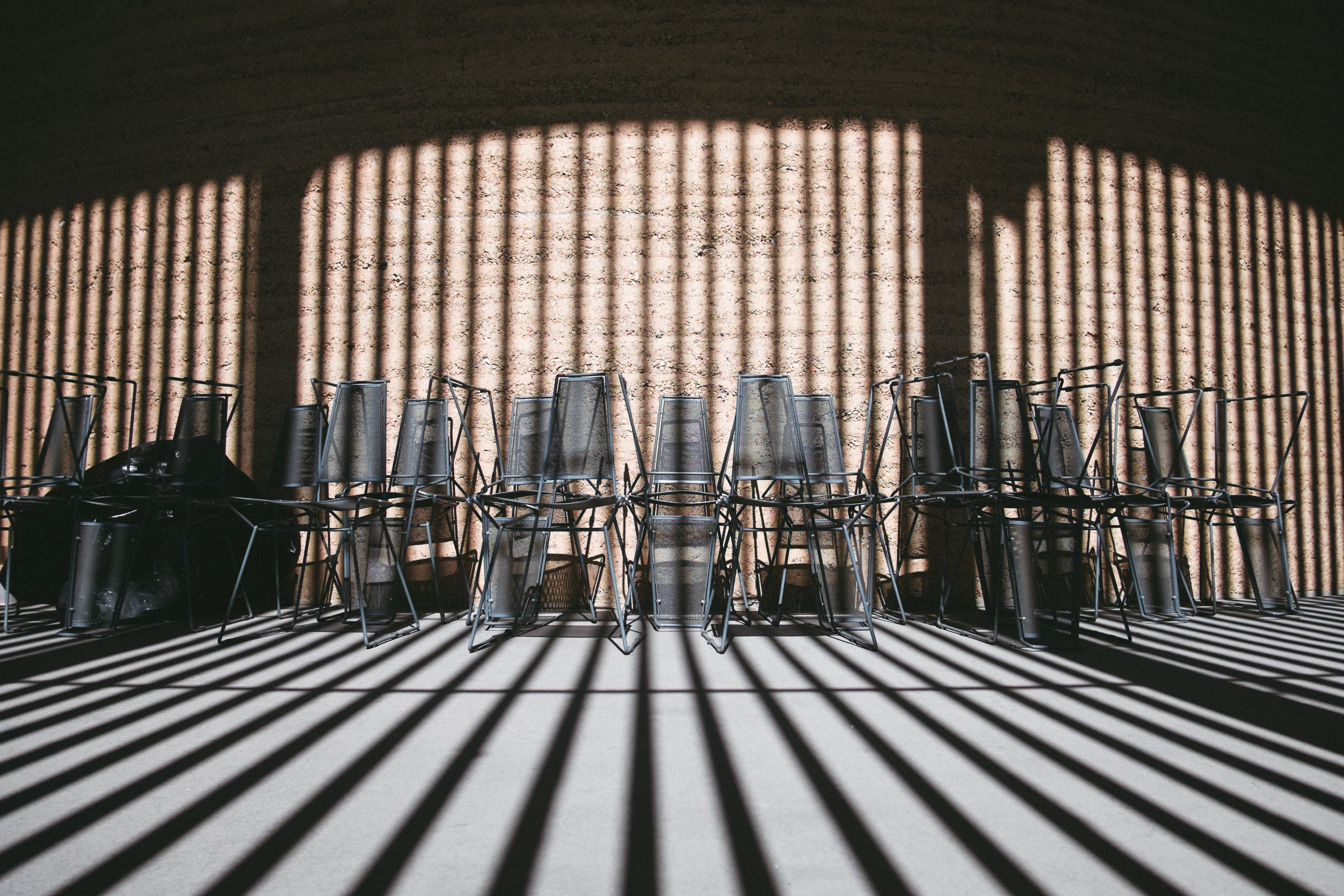 Stacked chairs along the wall covered by shadows of the building
