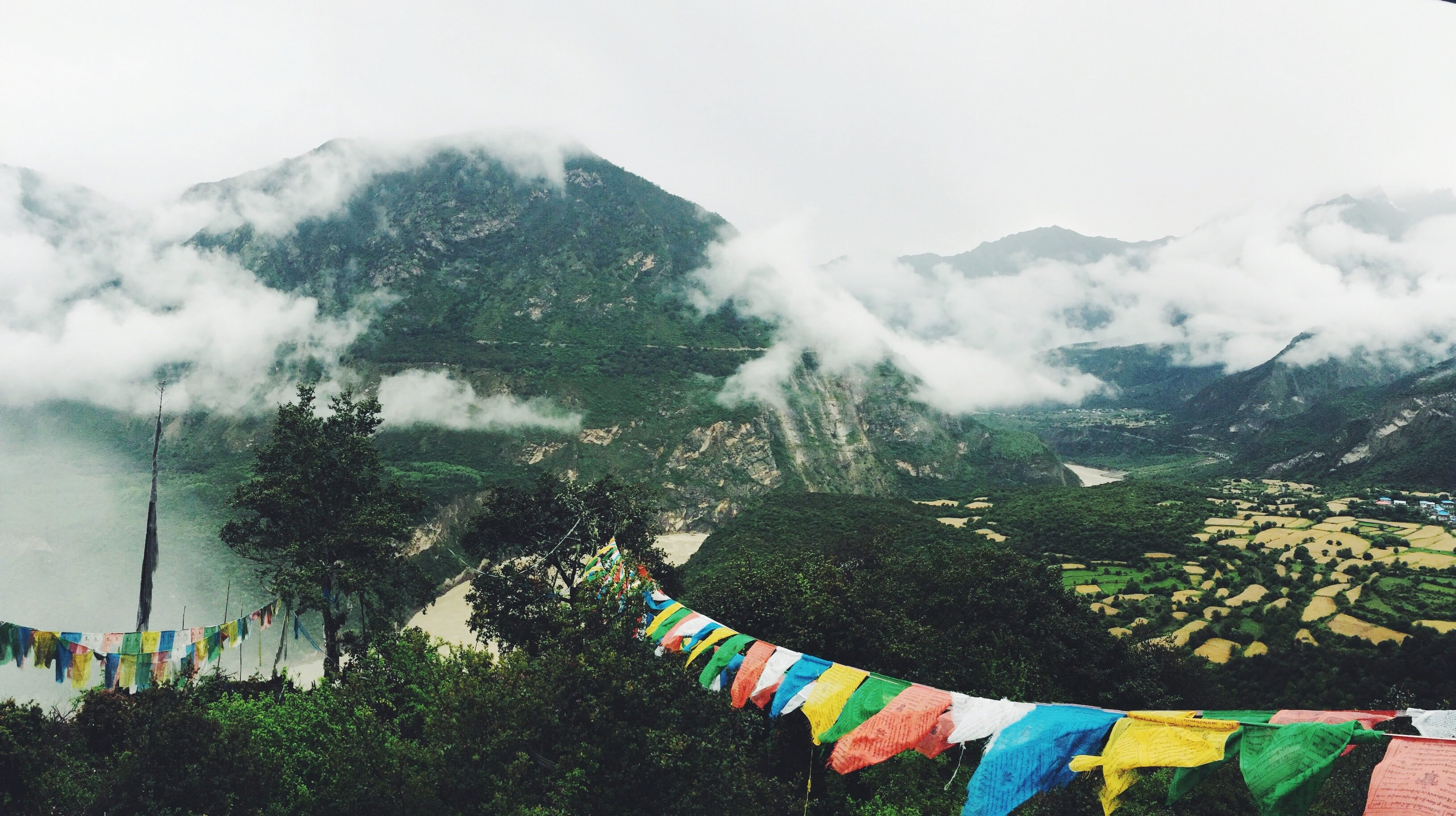 Colorful bunting hanging between treetops with view on a cloud-shrouded mountain
