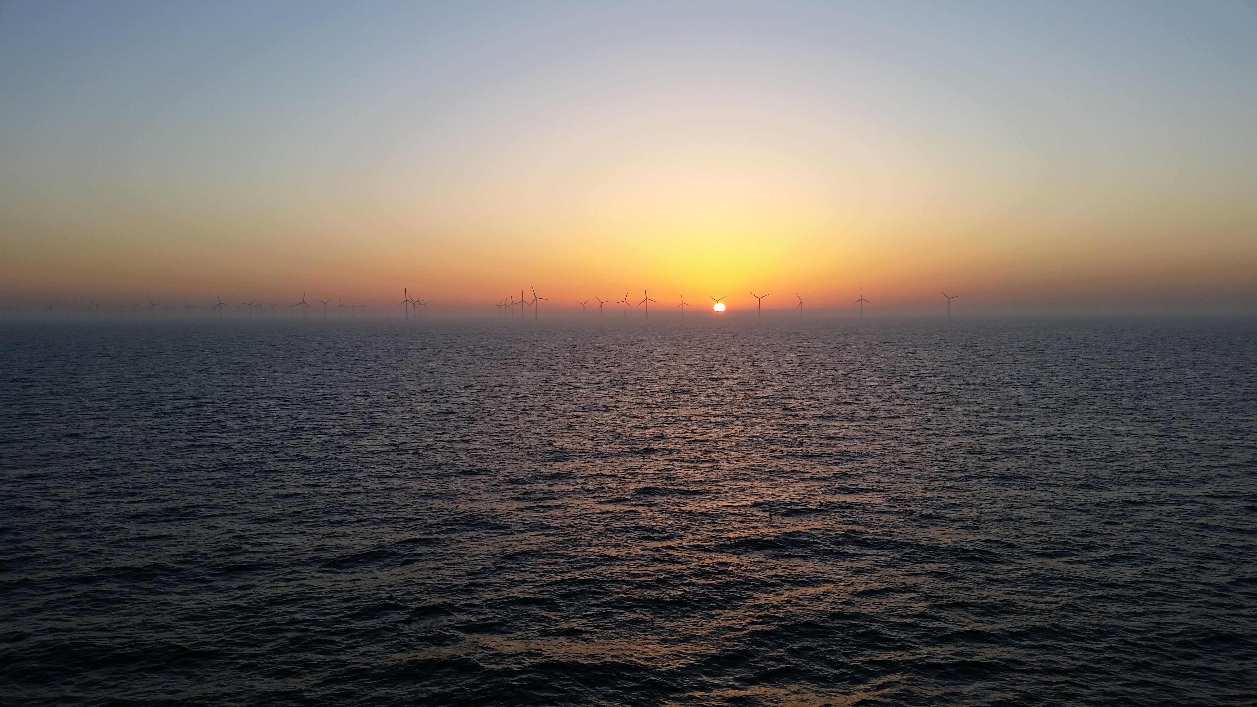 View of the sea during sunset and wind turbines visible at the horizon