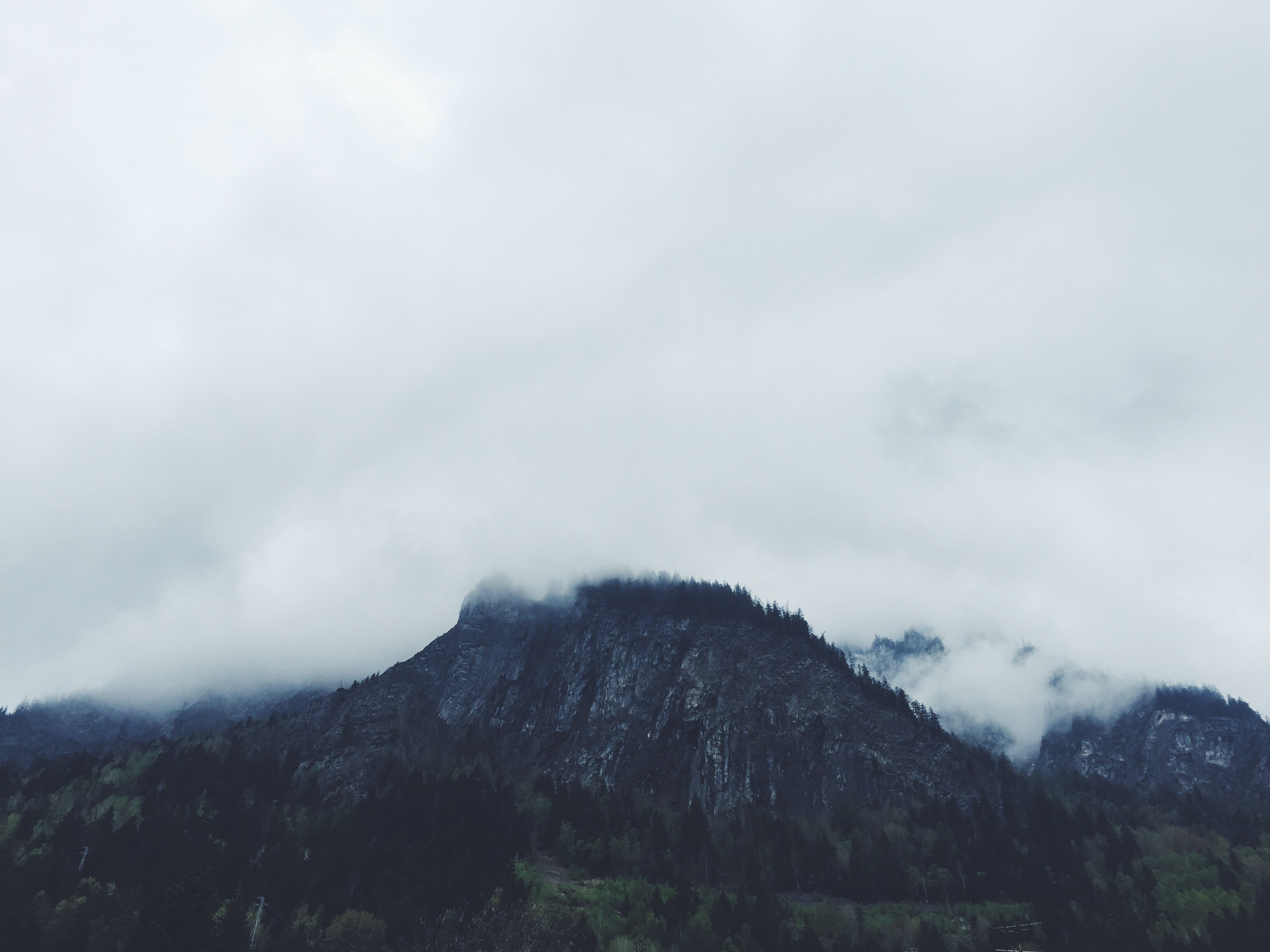A jagged mountain shrouded in fog on a cloudy day