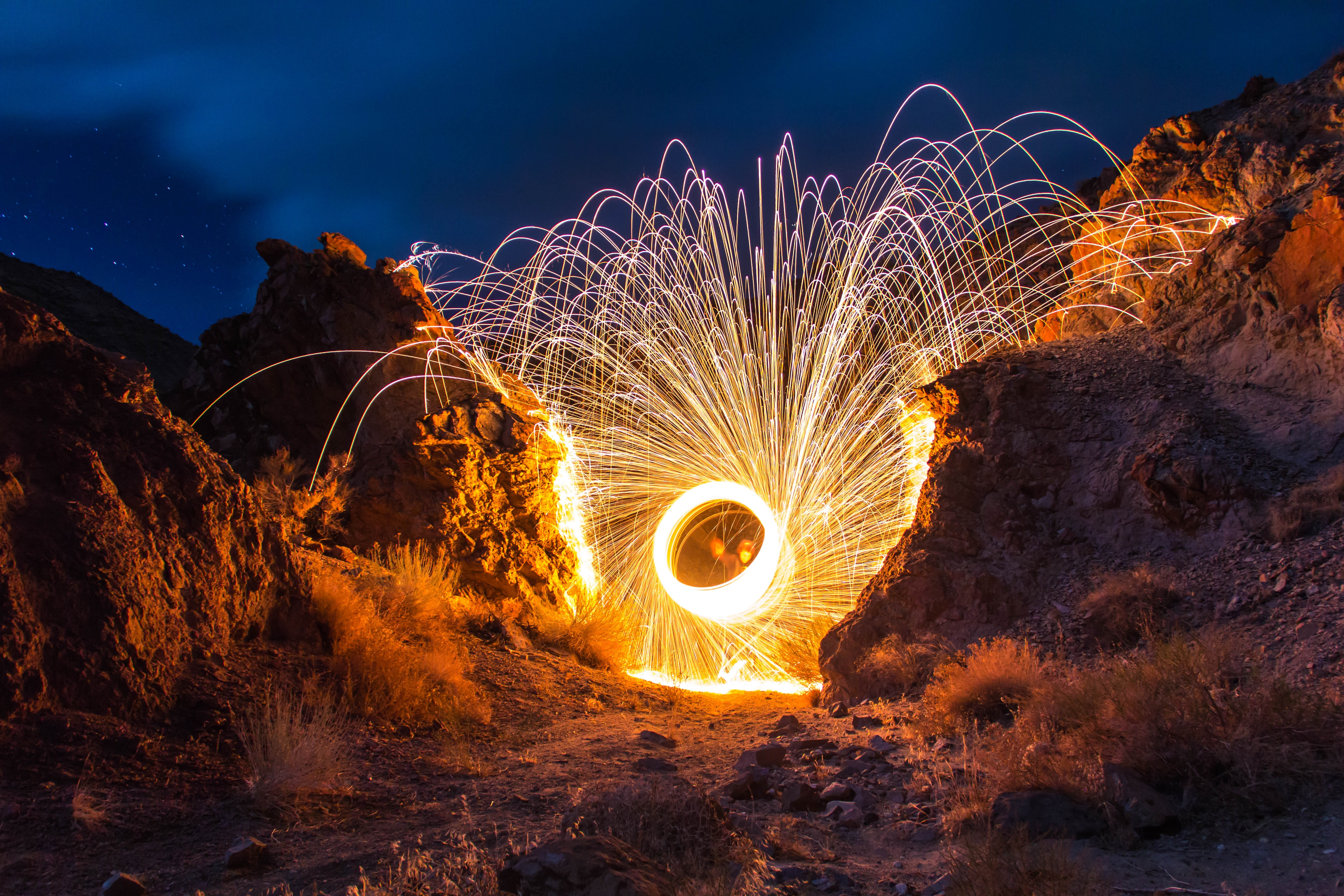 Bright spiral firework at night in mountains on dusty landscape