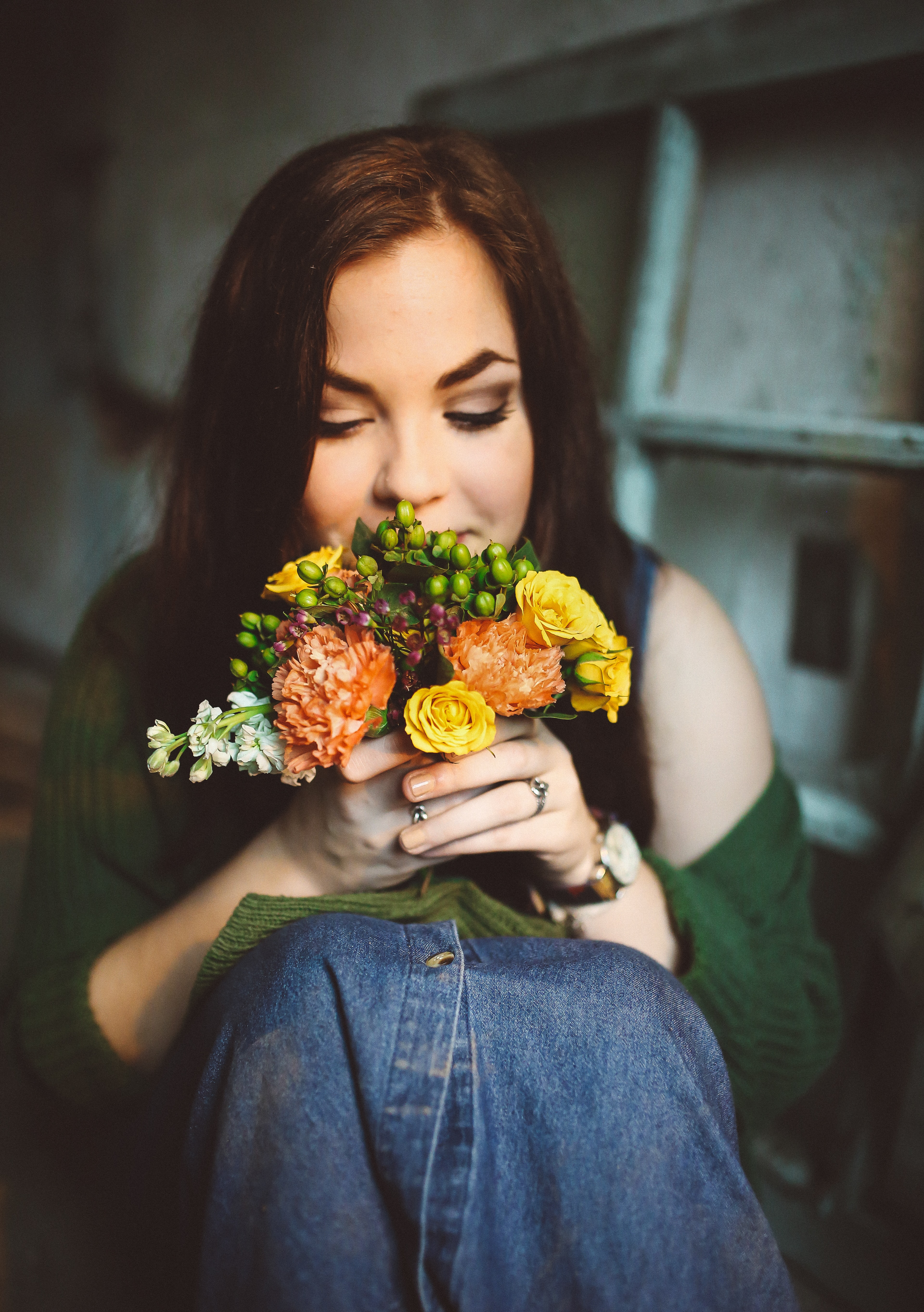 A young woman sitting on the floor and smelling a small bouquet of flowers