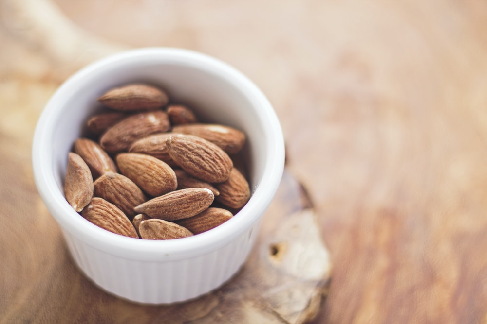 shallow focus photography of almonds in white ceramic bowl