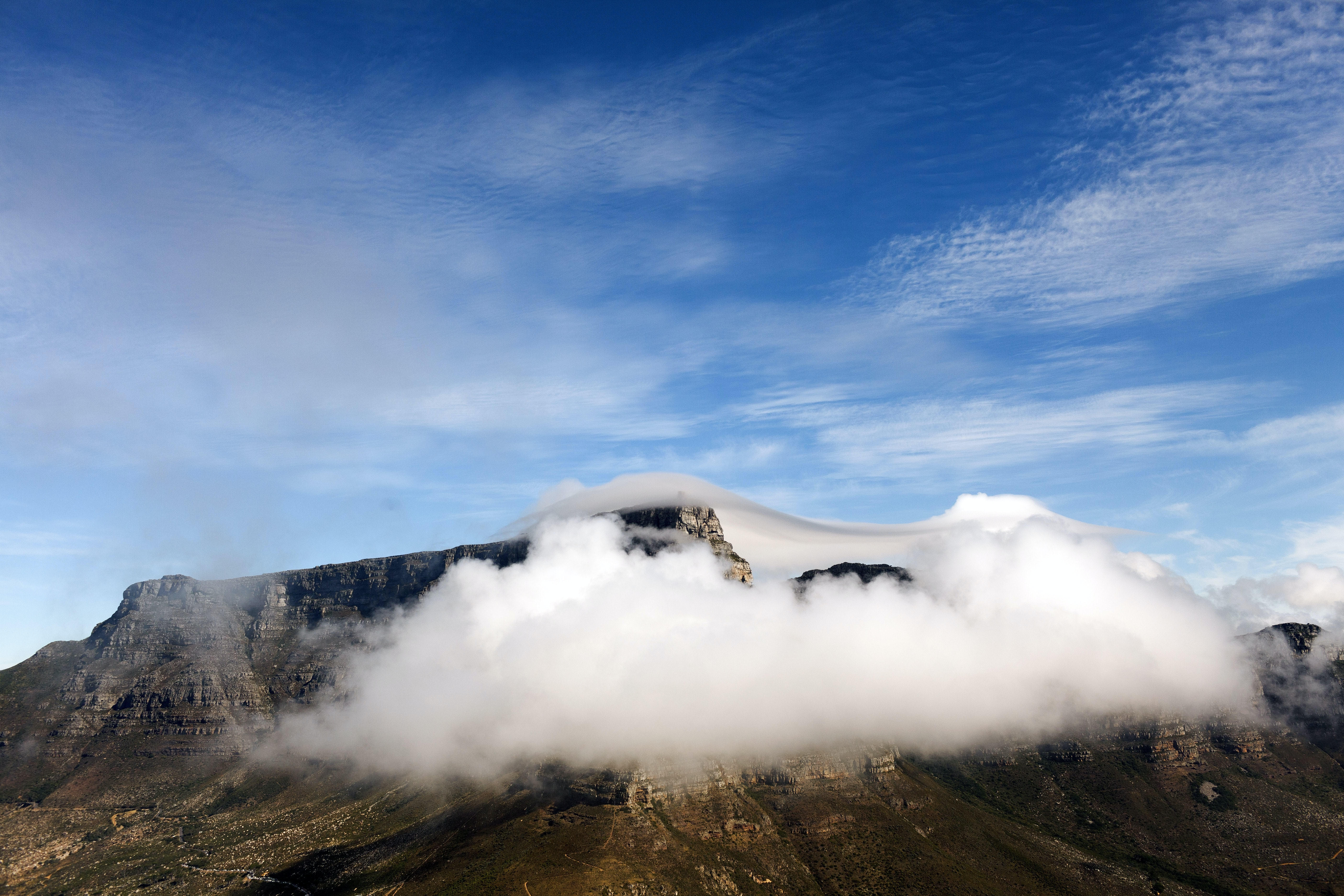 A fluffy cloud enveloping a rocky mountaintop on a bright day