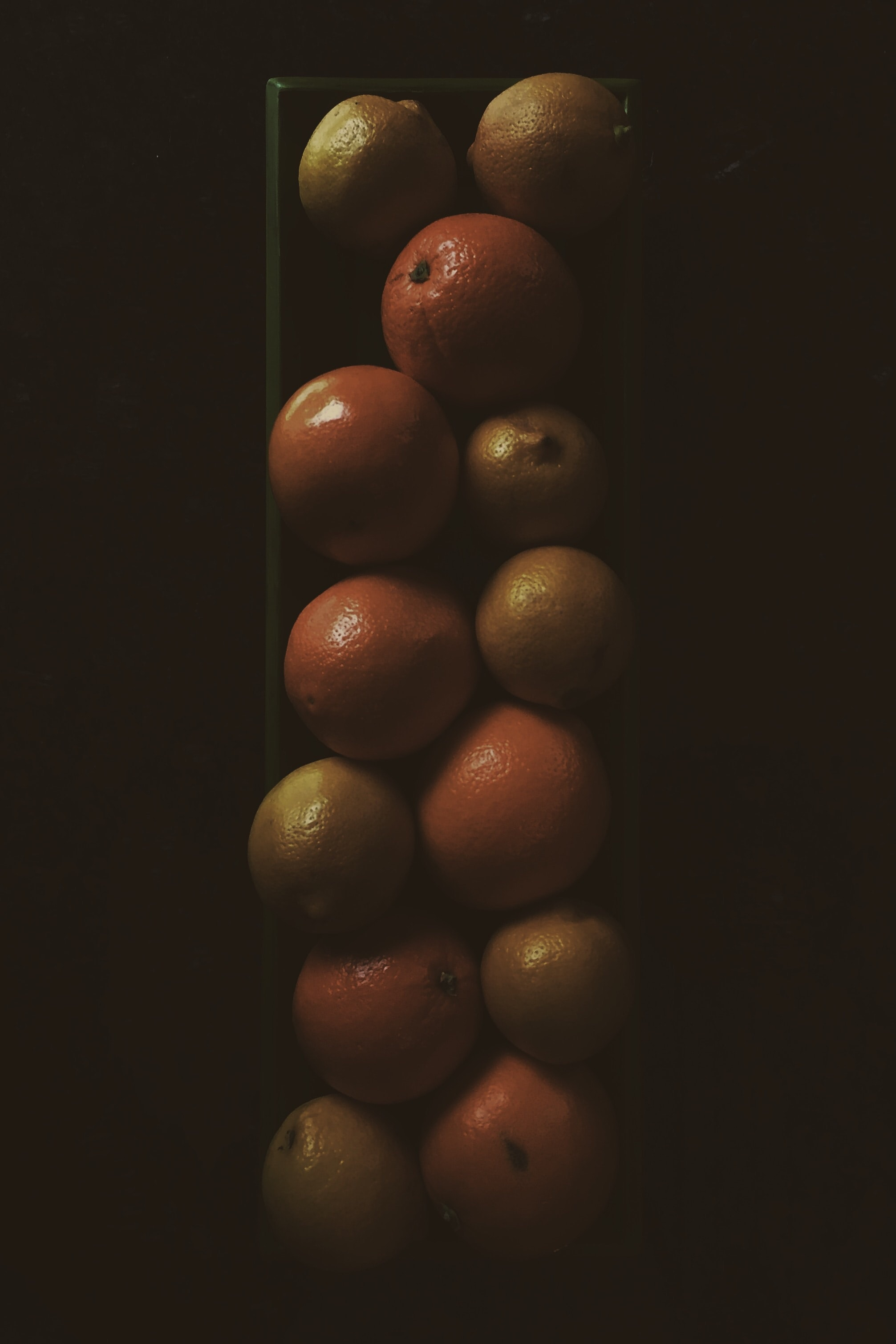 Stack of lemons, oranges, and citrus fruit in a glass vase