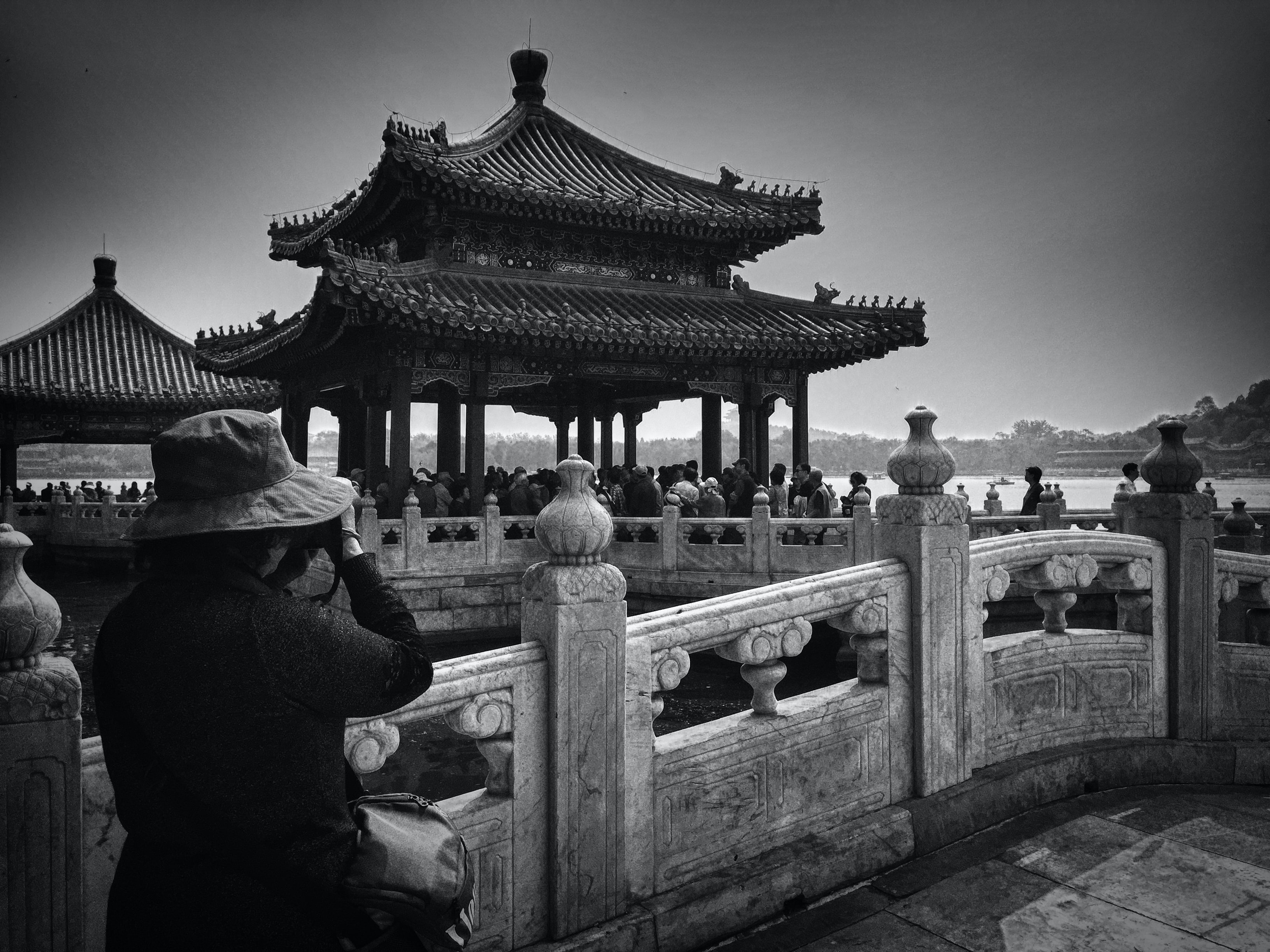 grayscale photo of woman taking photo of temple with people