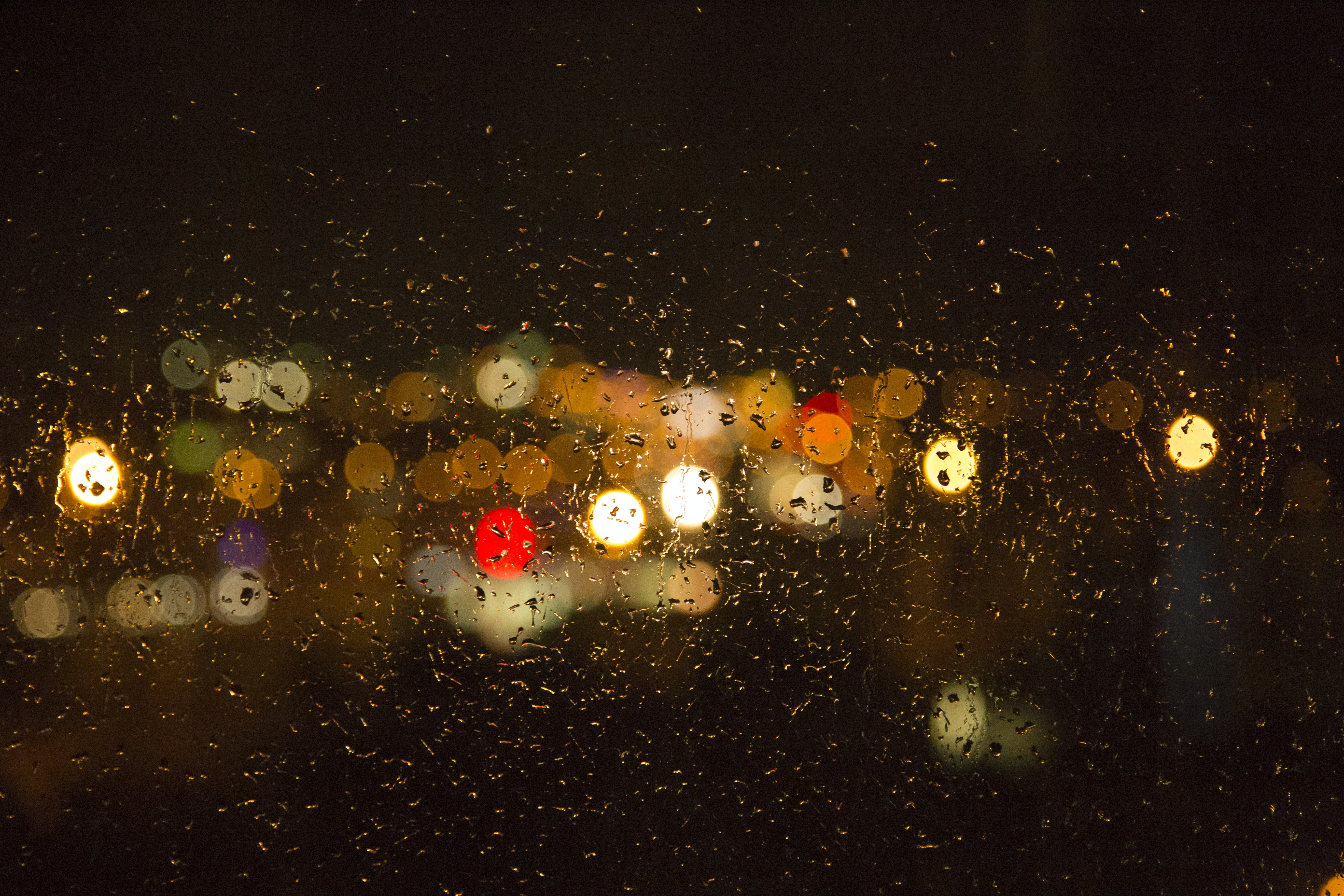 A blurry view of traffic at night, taken from behind a rain covered windshield.