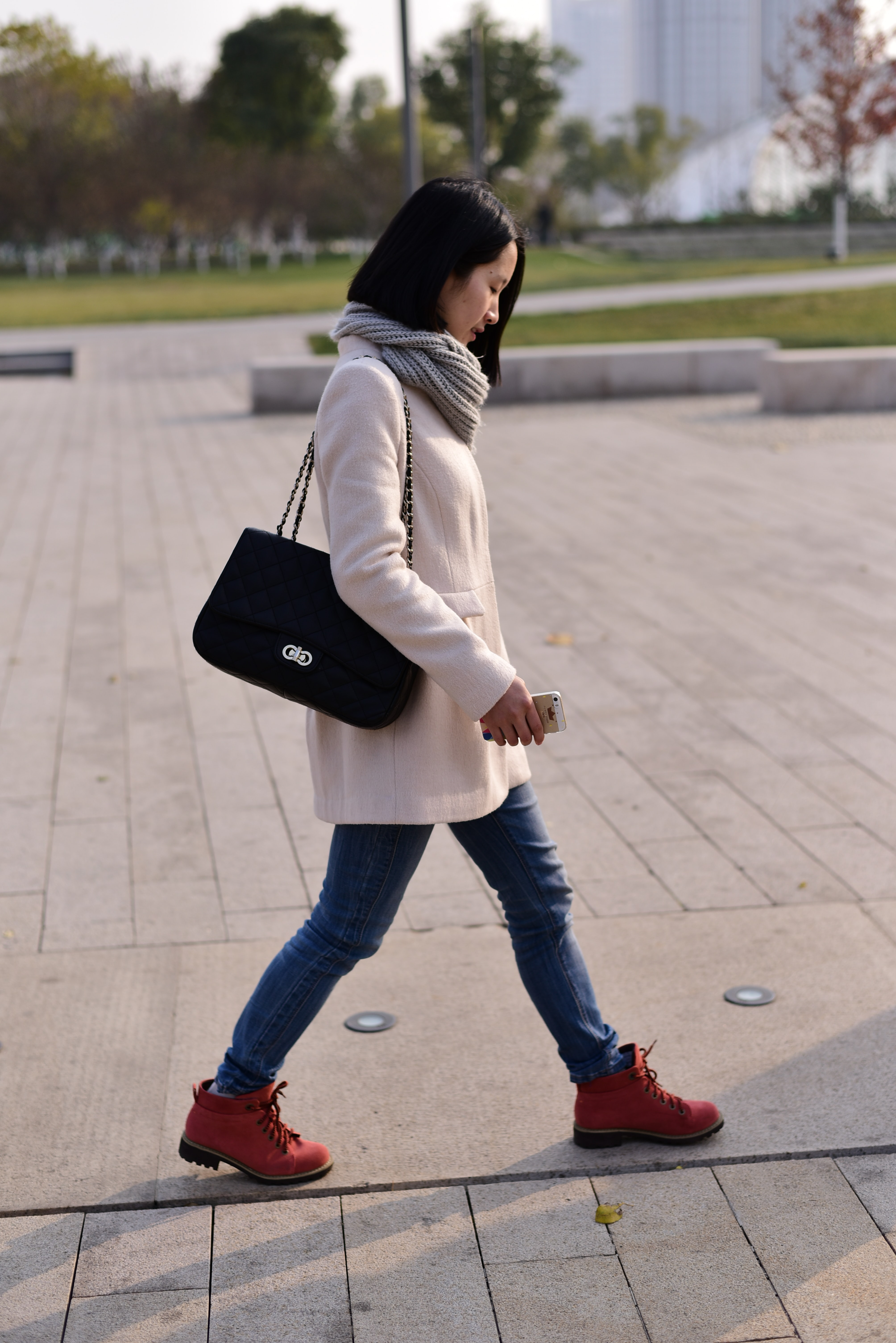 Woman in a knit scarf and sweater walking and carrying an iphone