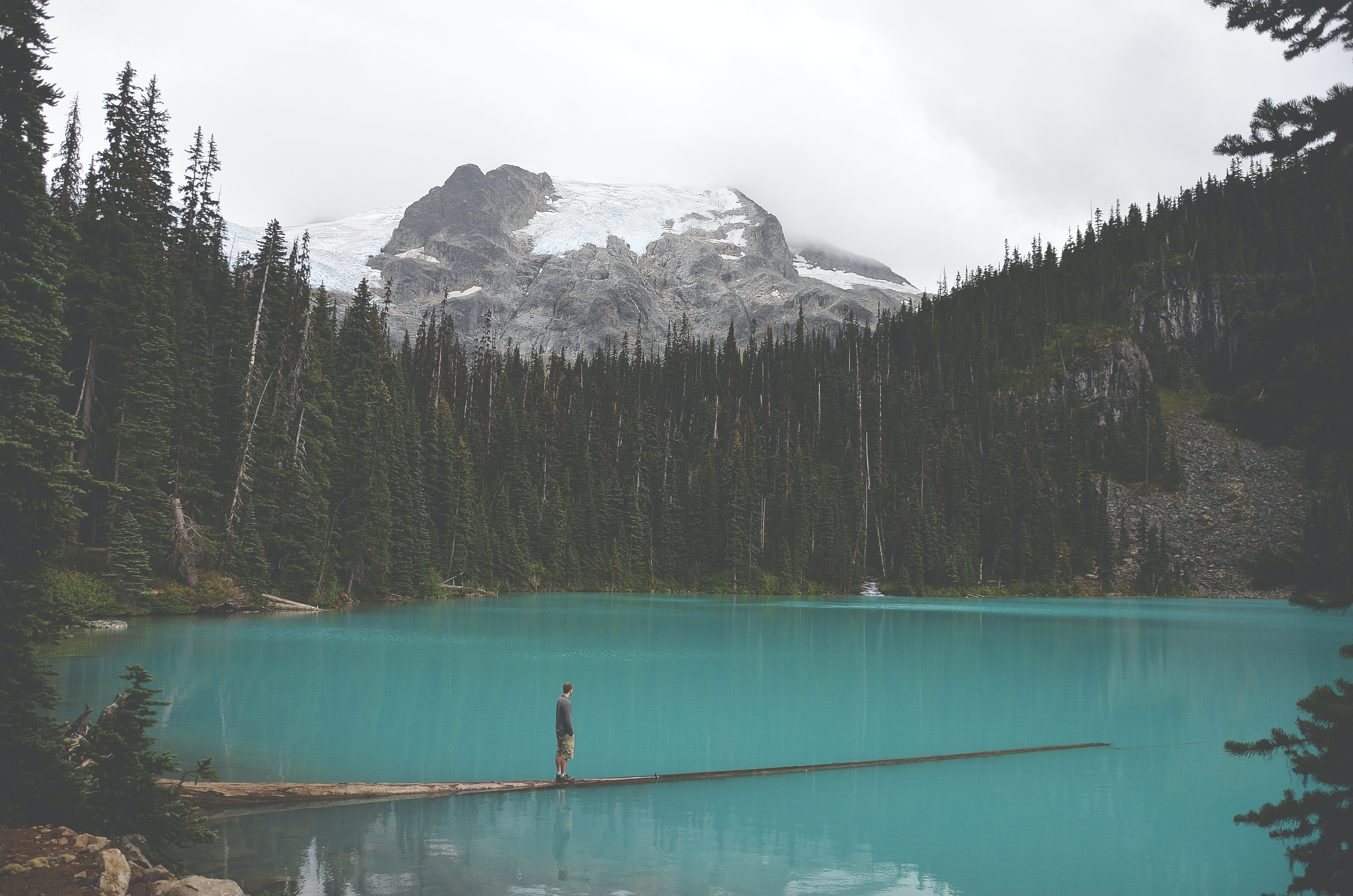 A man at a lake surrounded by trees and big rock covered in snow