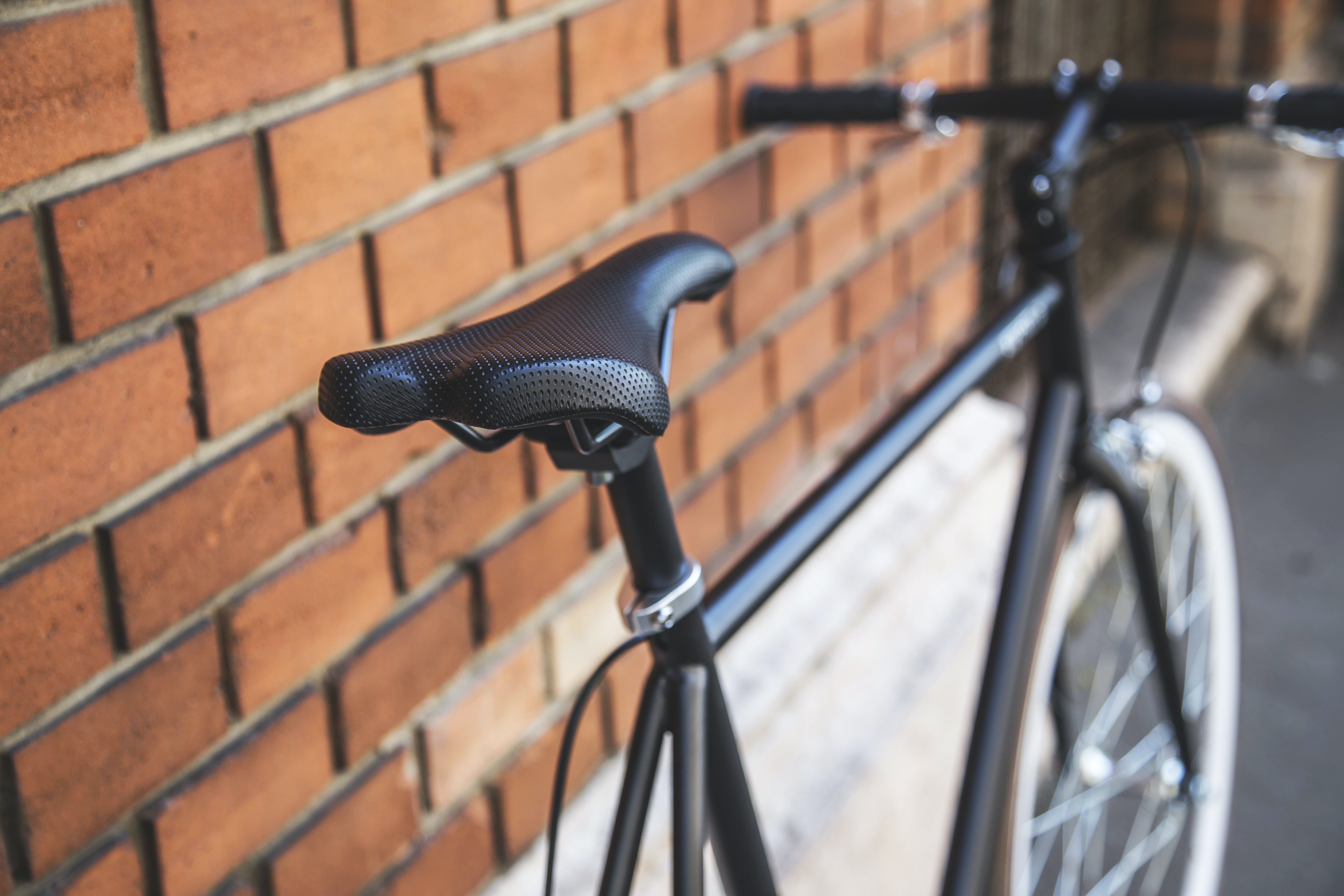 Black bicycle parked against a brick wall