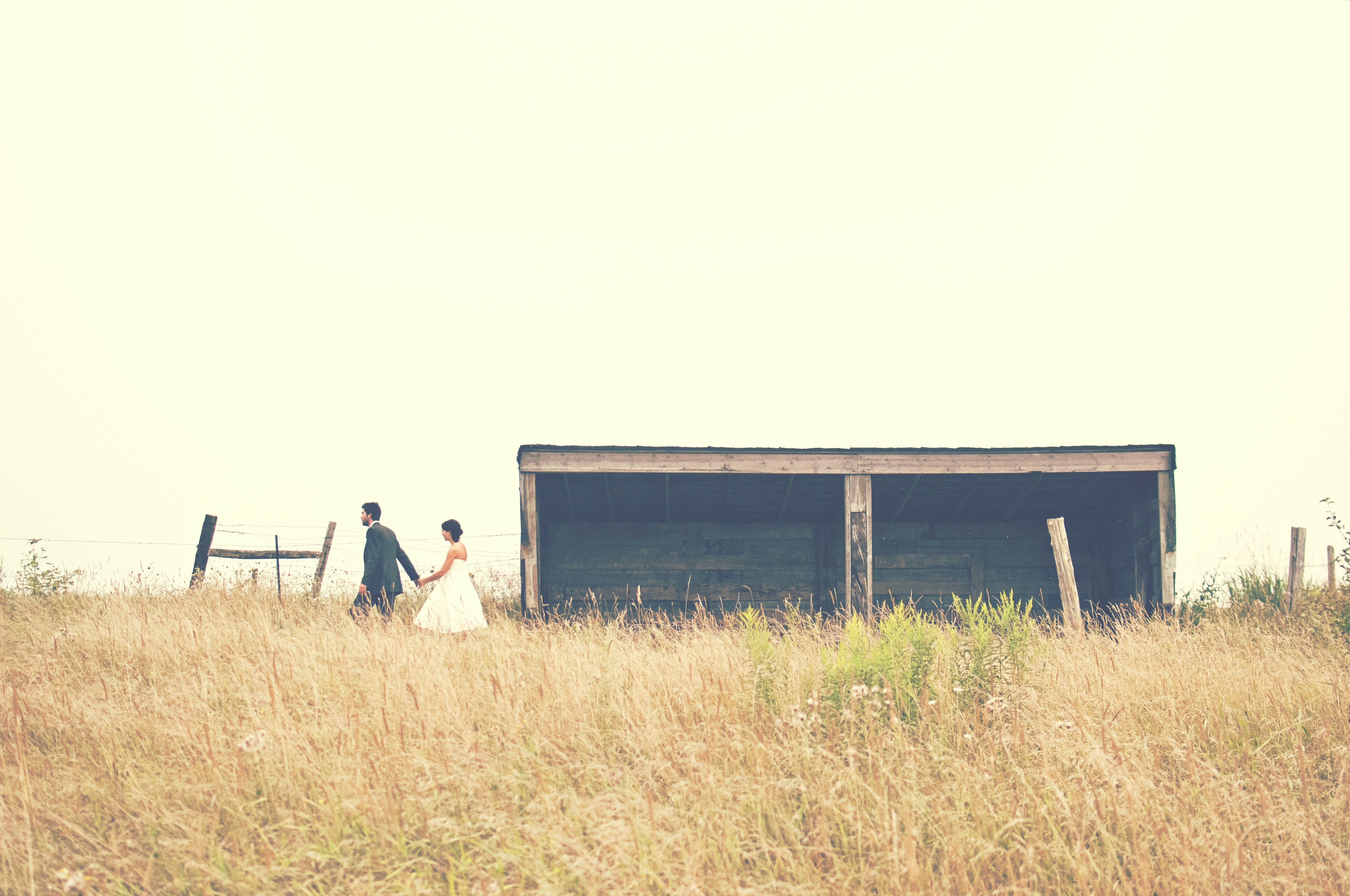 Wedding day photo in a field beside an old wooden farm building