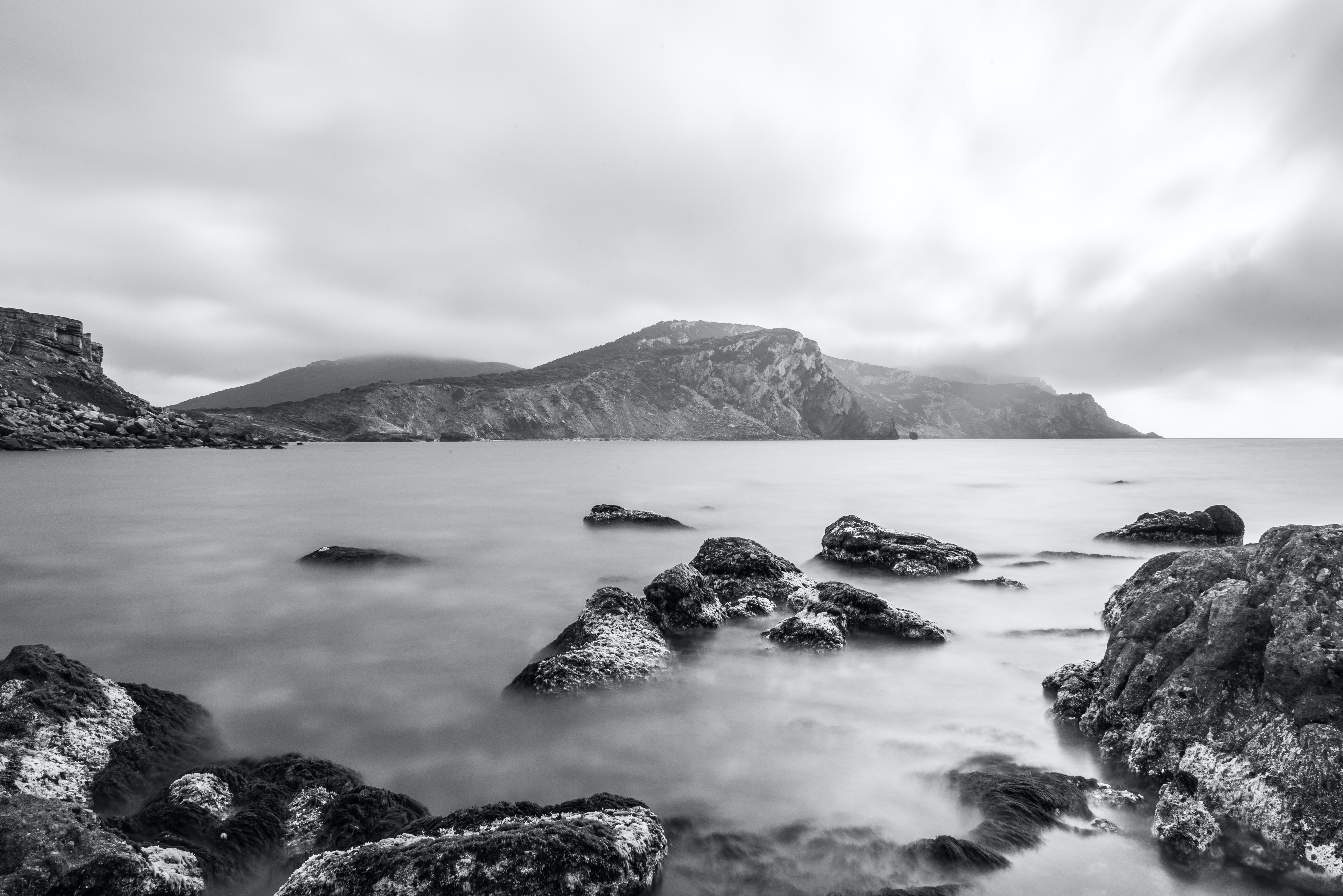 A black-and-white shot of mossy rocks jutting out from the water with rocky cliffs at the back