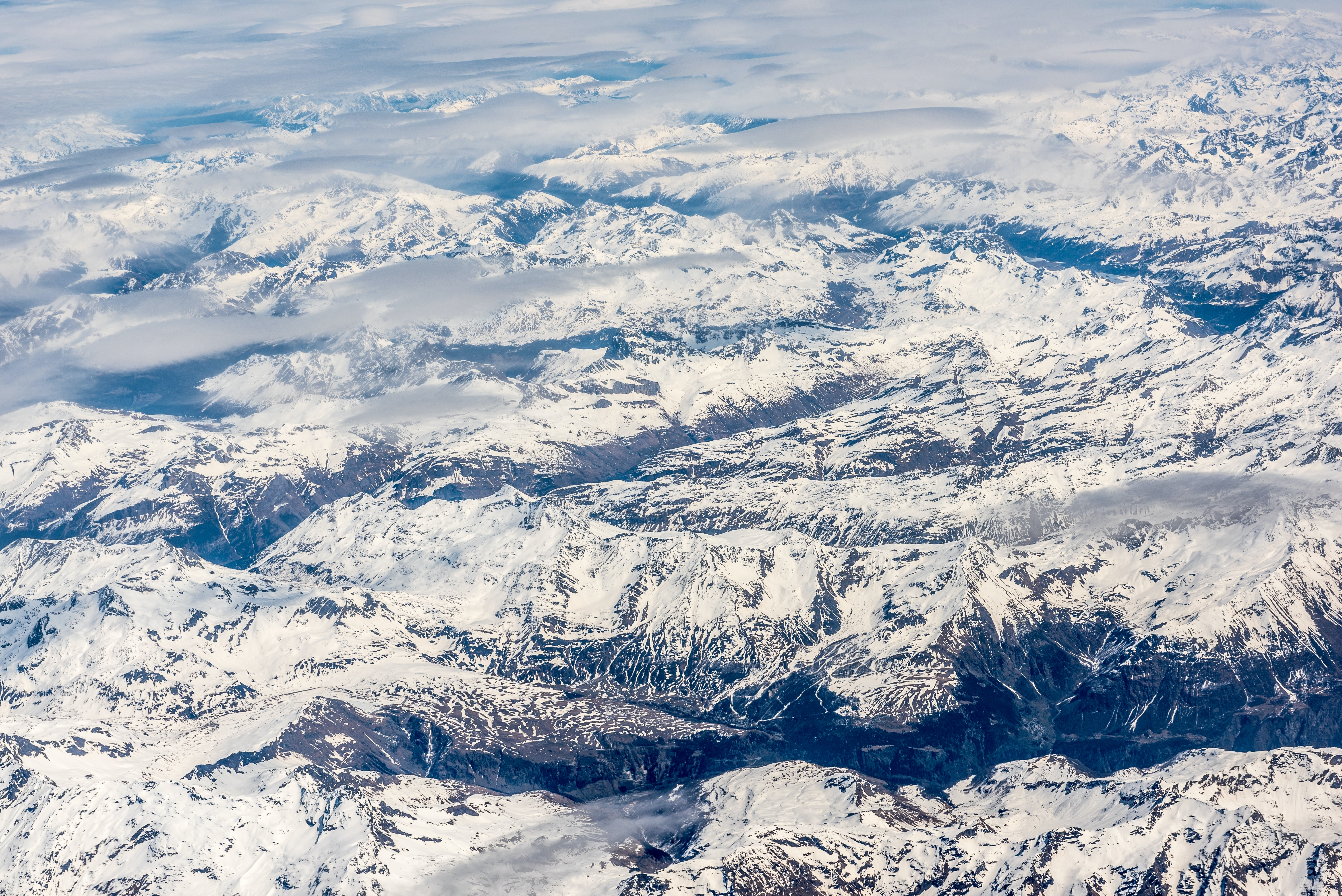 An aerial shot of a snowy mountain range under patchy clouds