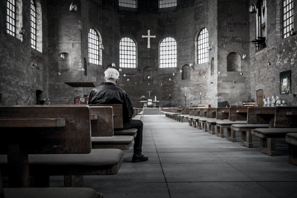 person sitting on pew inside church