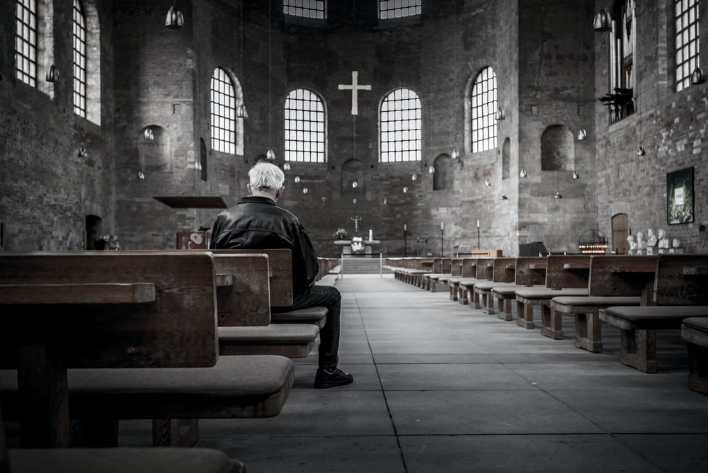 person sitting on pew inside church