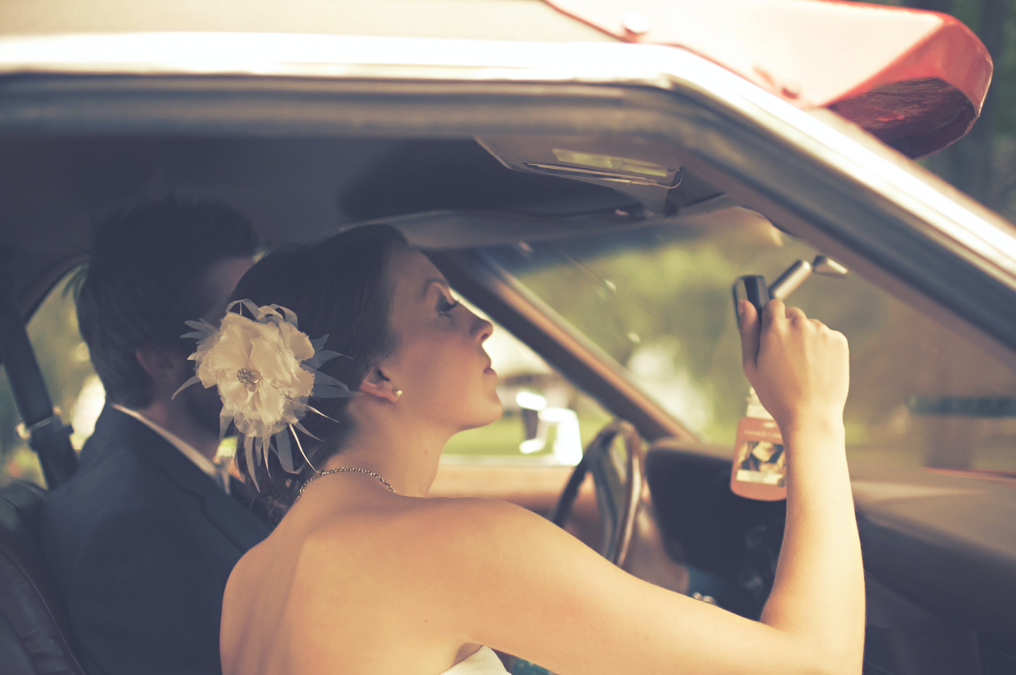 Wedding shot of young bride with flowerette and groom in suit sitting in car