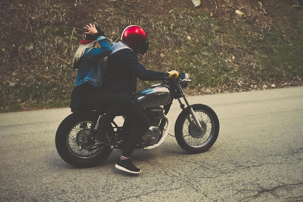 man and woman riding on cruiser motorcycle at blacktop road