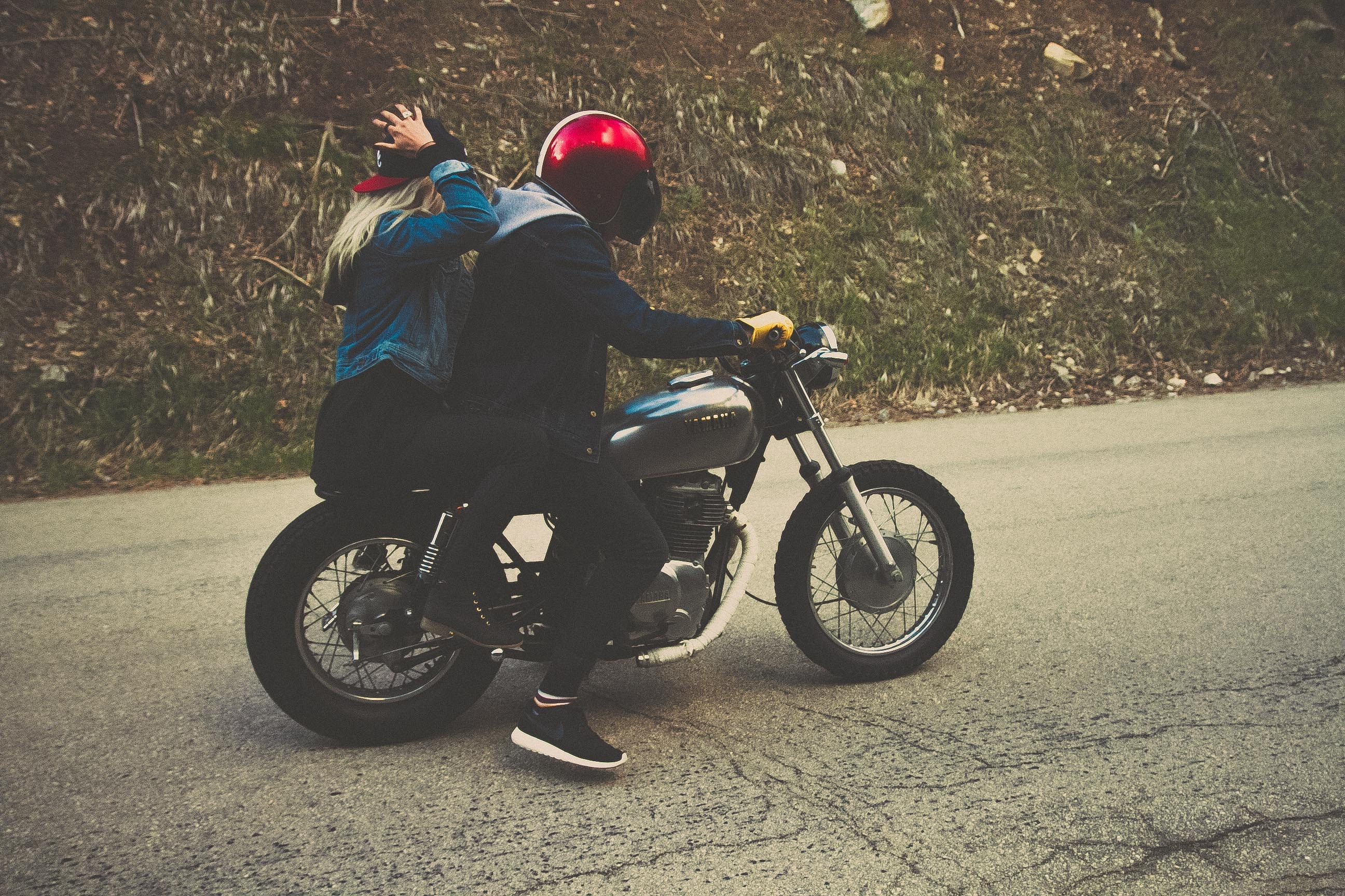Two people on a silver motorcycle on asphalt