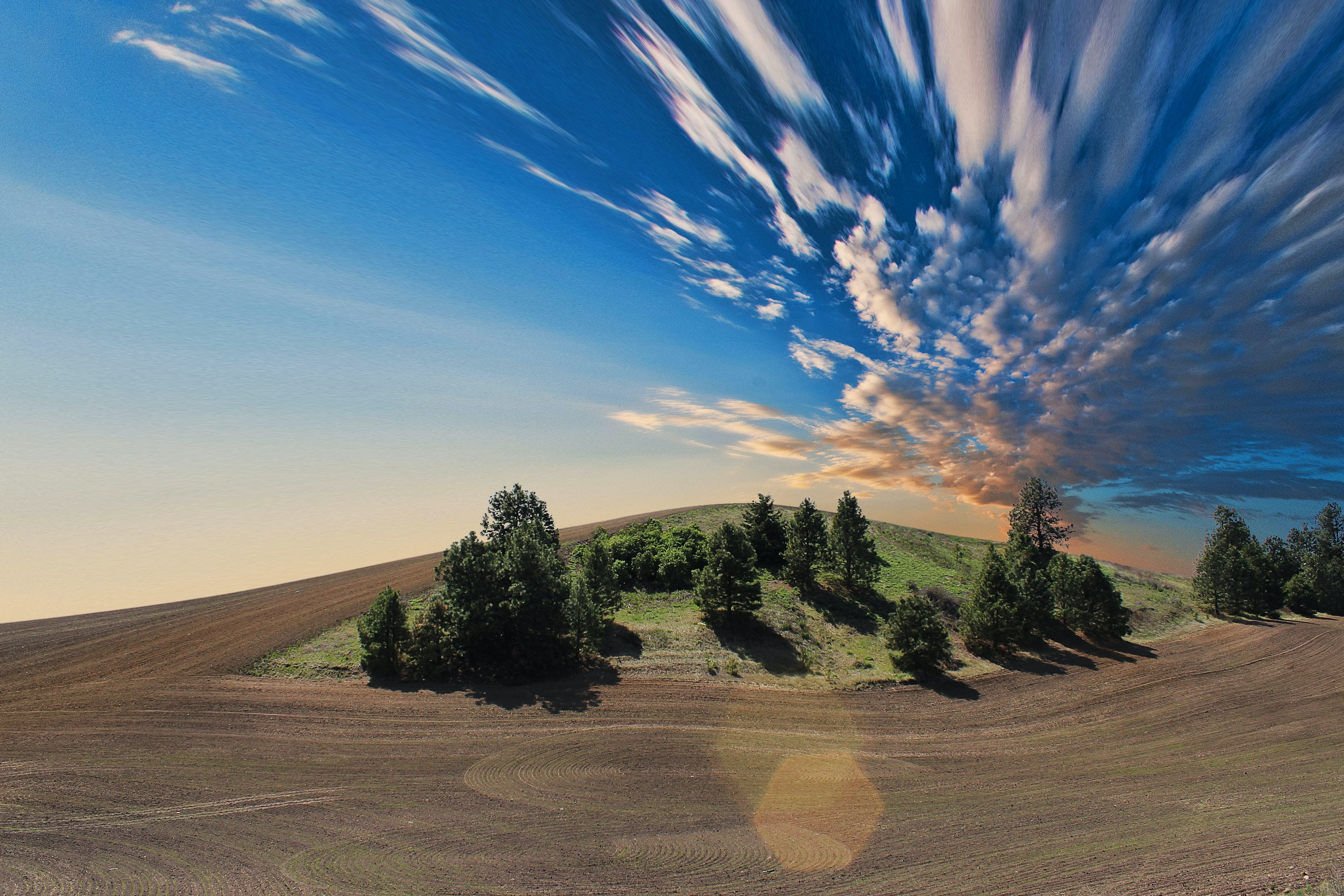A bizarre shot of a plowed field with a patch of trees and clouds rapidly moving across the sky