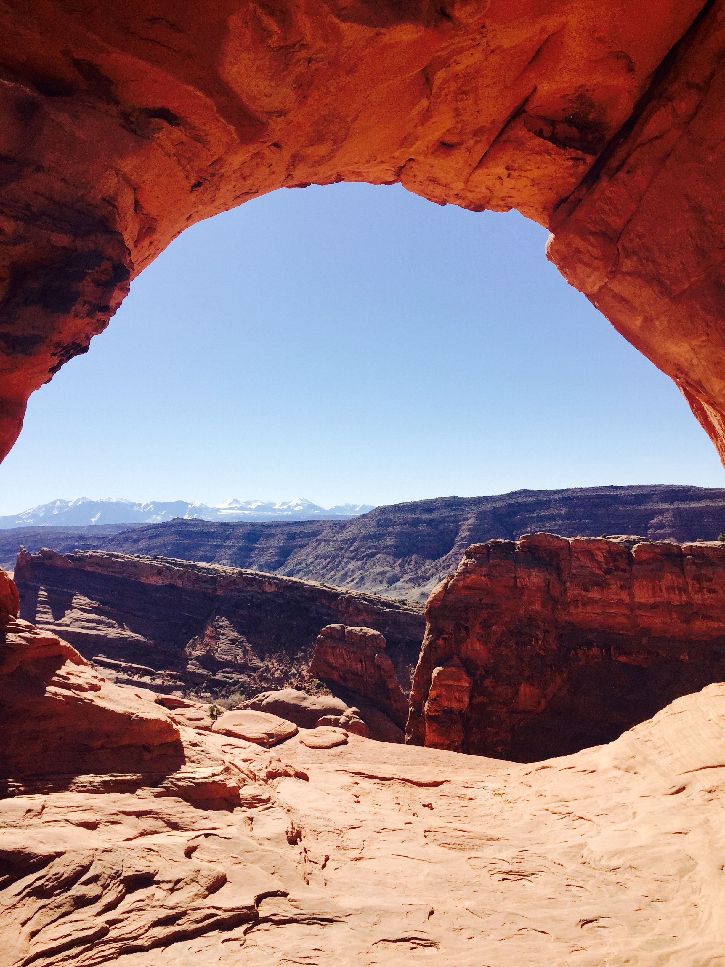 A view on a sunlit canyon from below a red rocky arch