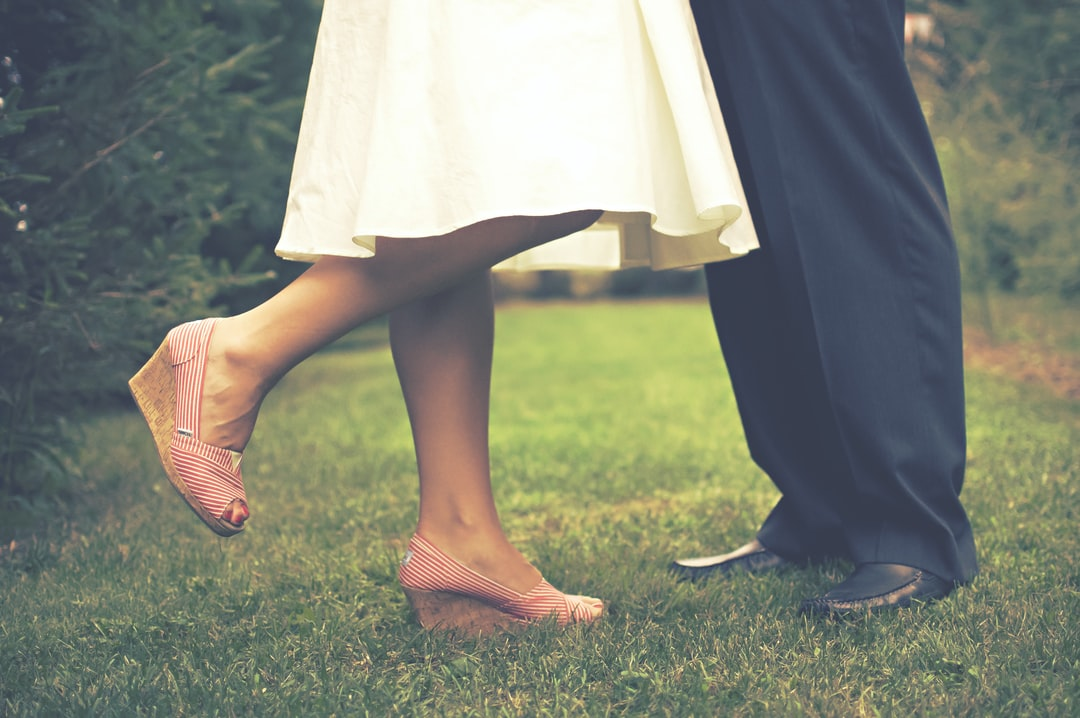Free high-res photo of bride and groom feet while kissing in grass