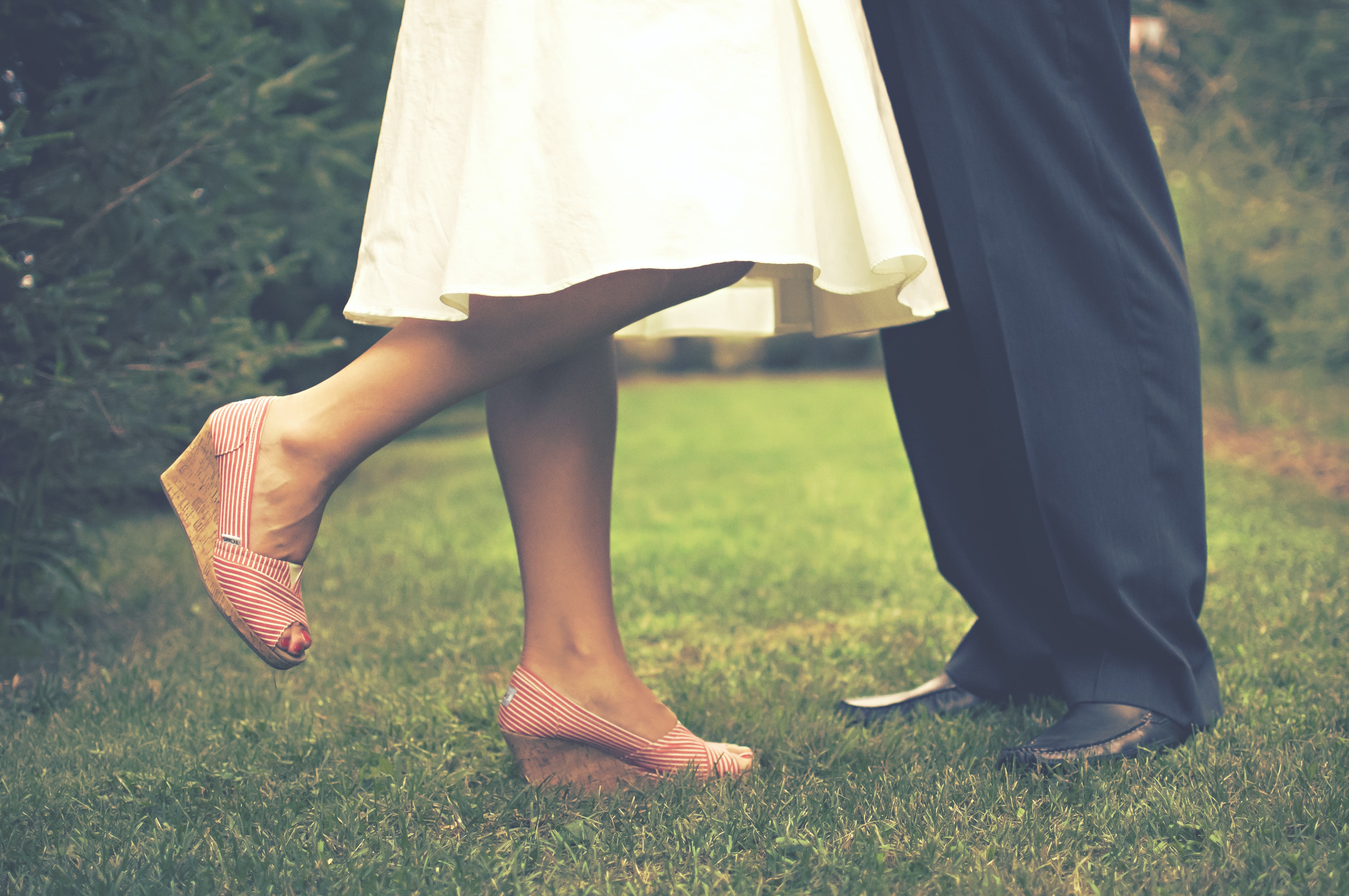 A bride and groom's legs in a short, white dress and pink wedges and black suit