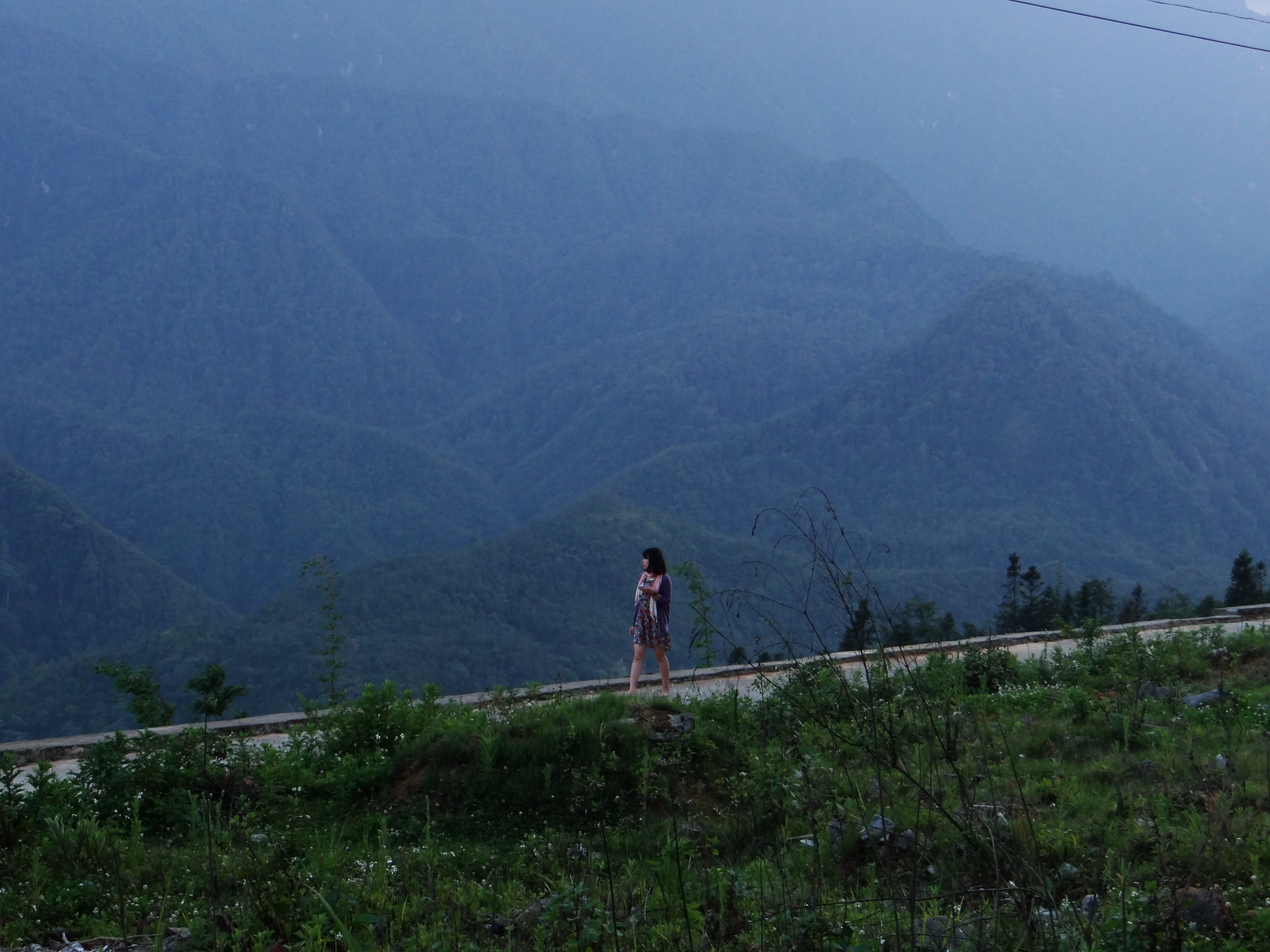A dark-haired woman walking across a path with lush undulating hills behind her