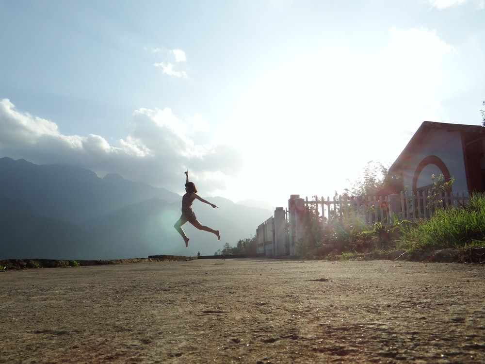 woman jumping at daytime near house