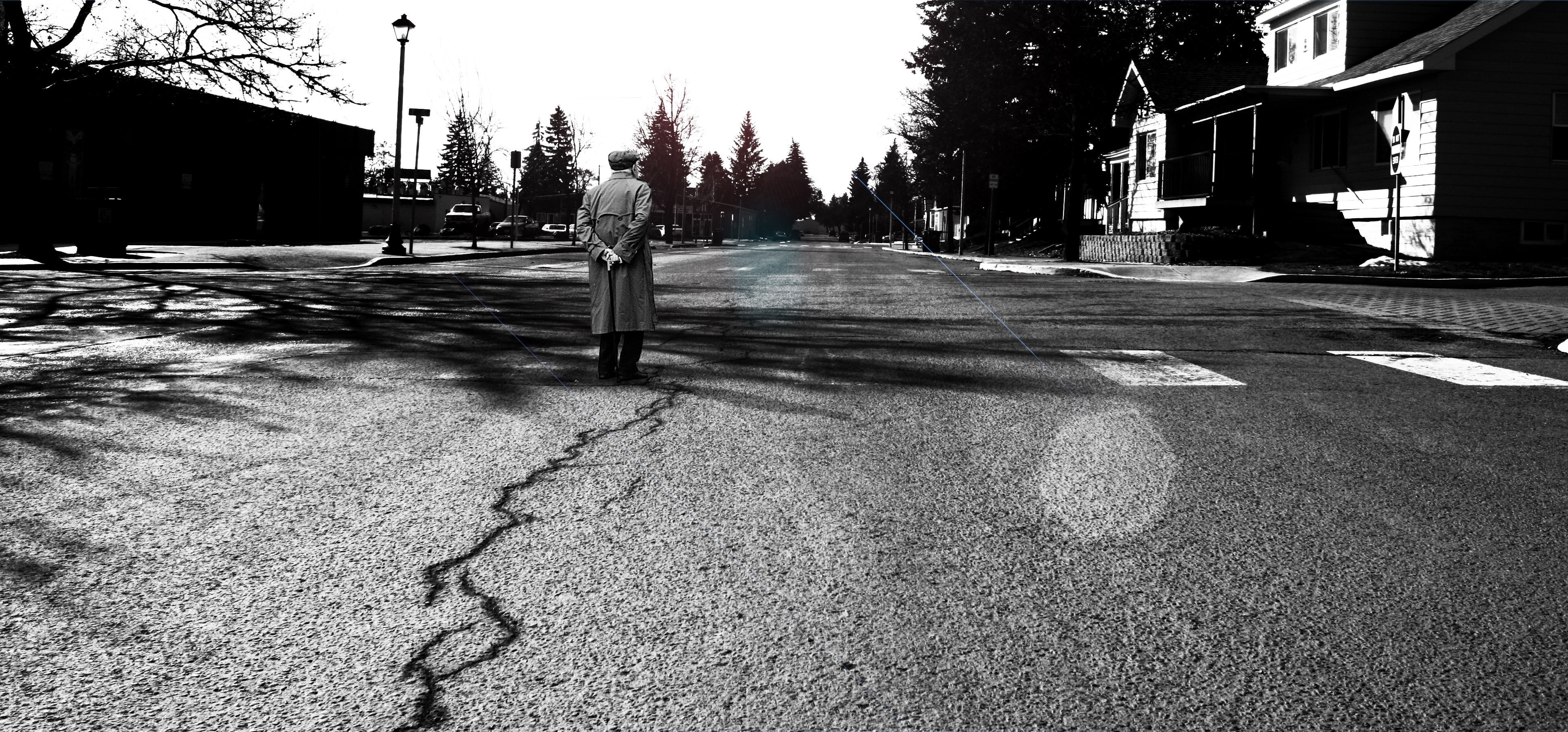 An elderly man walks in the middle of an old cracked street road with lamps and houses.