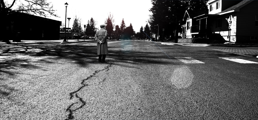 man standing in the middle of the road grayscale photography