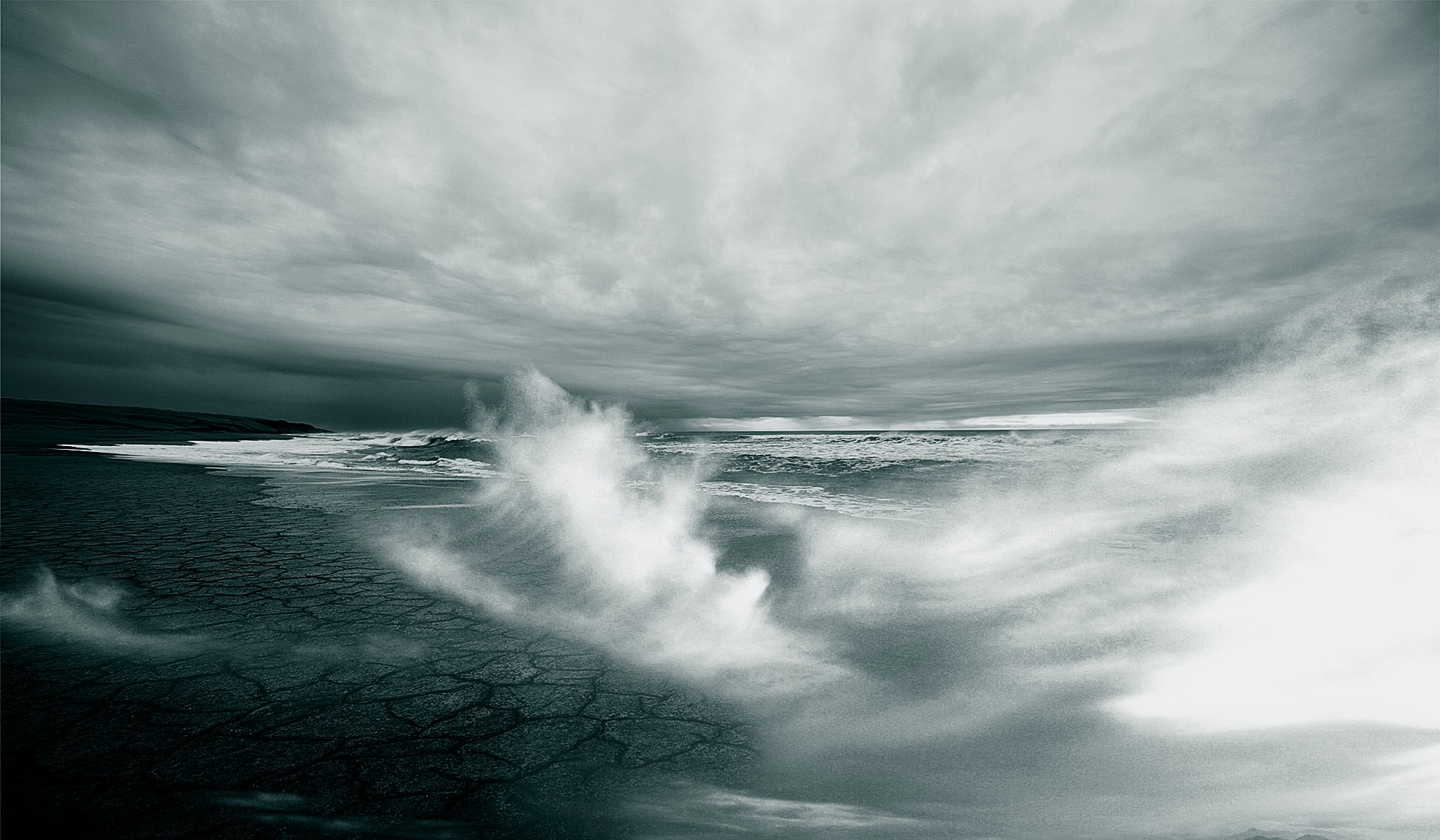White-capped sea waves breaking on a barren shore on a stormy day