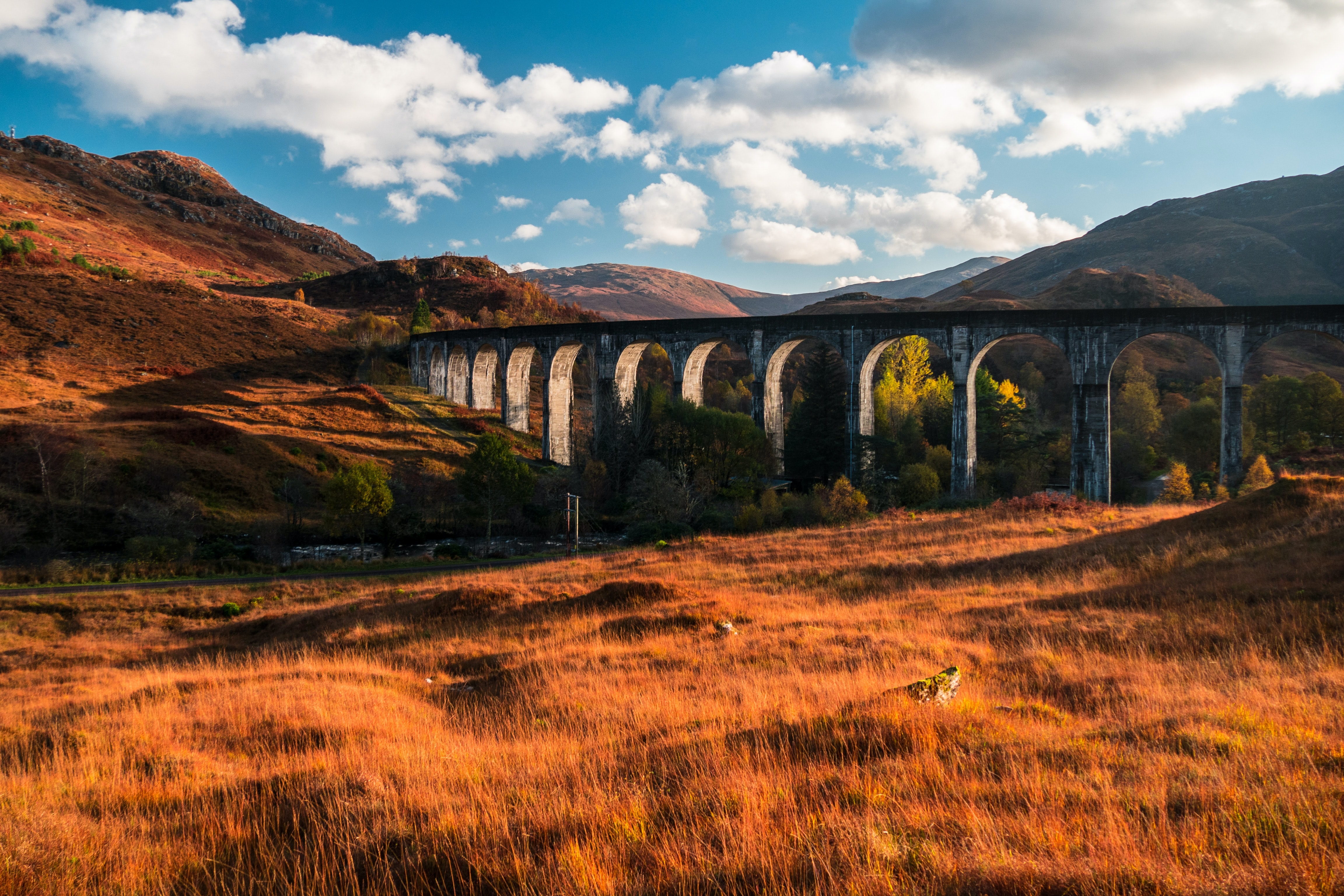 A concrete viaduct running through orange hilly grasslands on a sunny afternoon