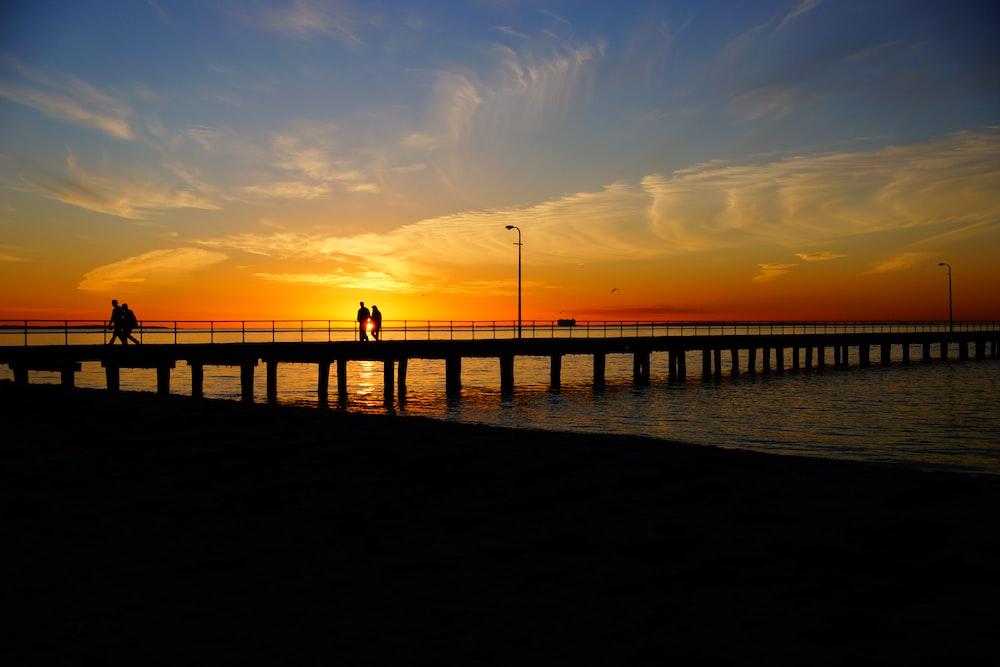 silhouette of people walking on bridge