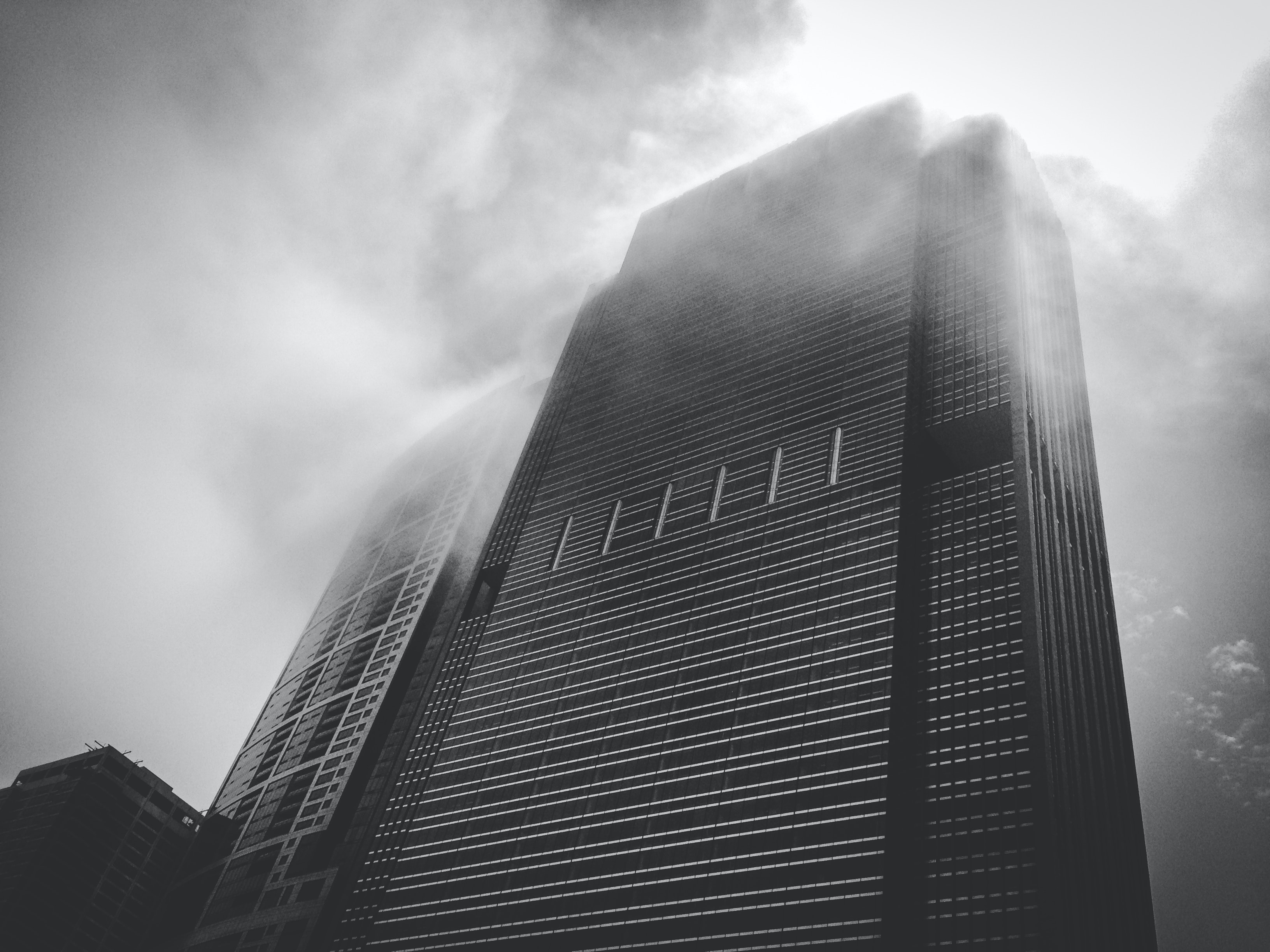 A black skyscraper shrouded in mist on a cloudy day