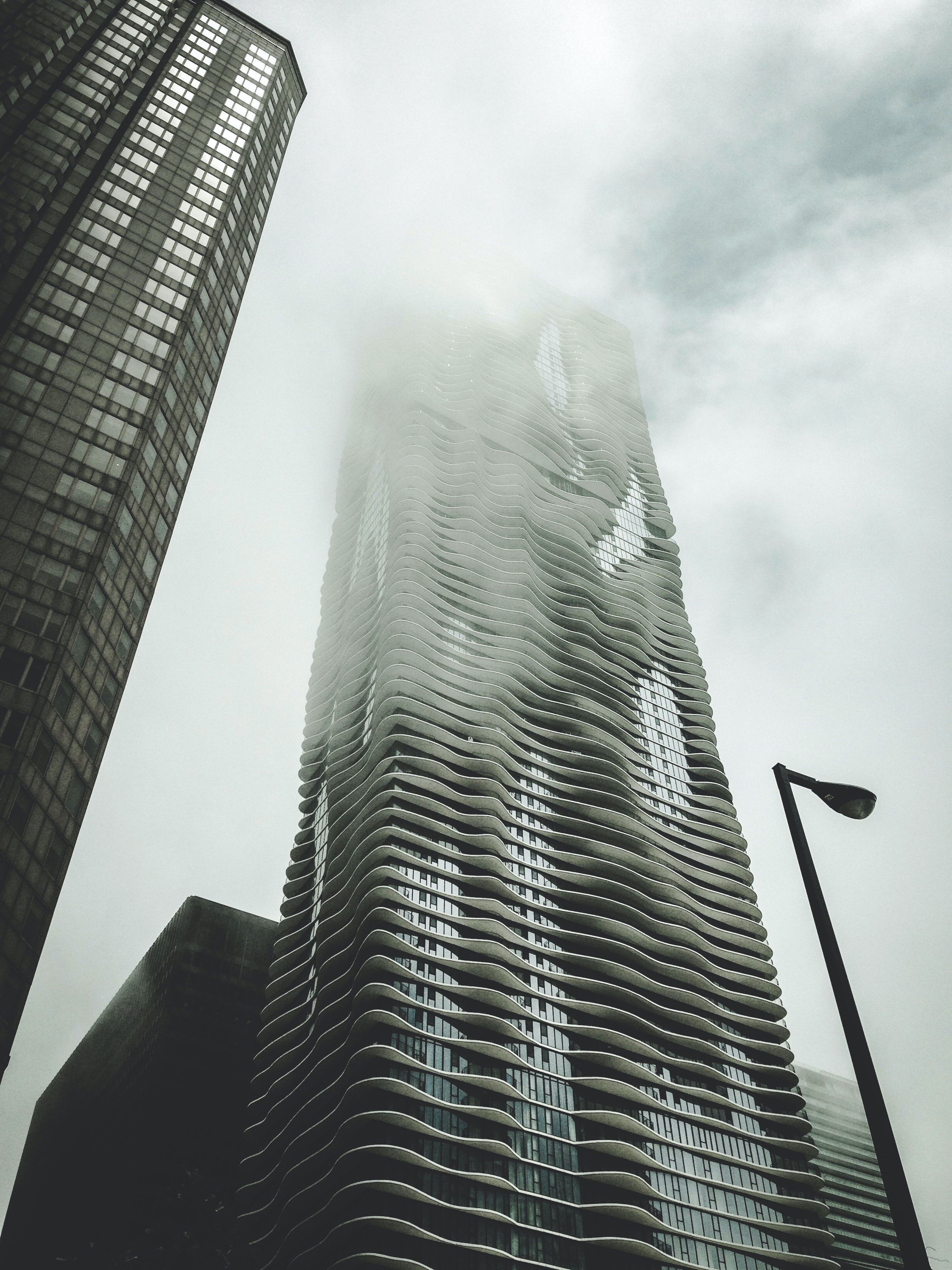 A tall skyscraper wreathed in mist