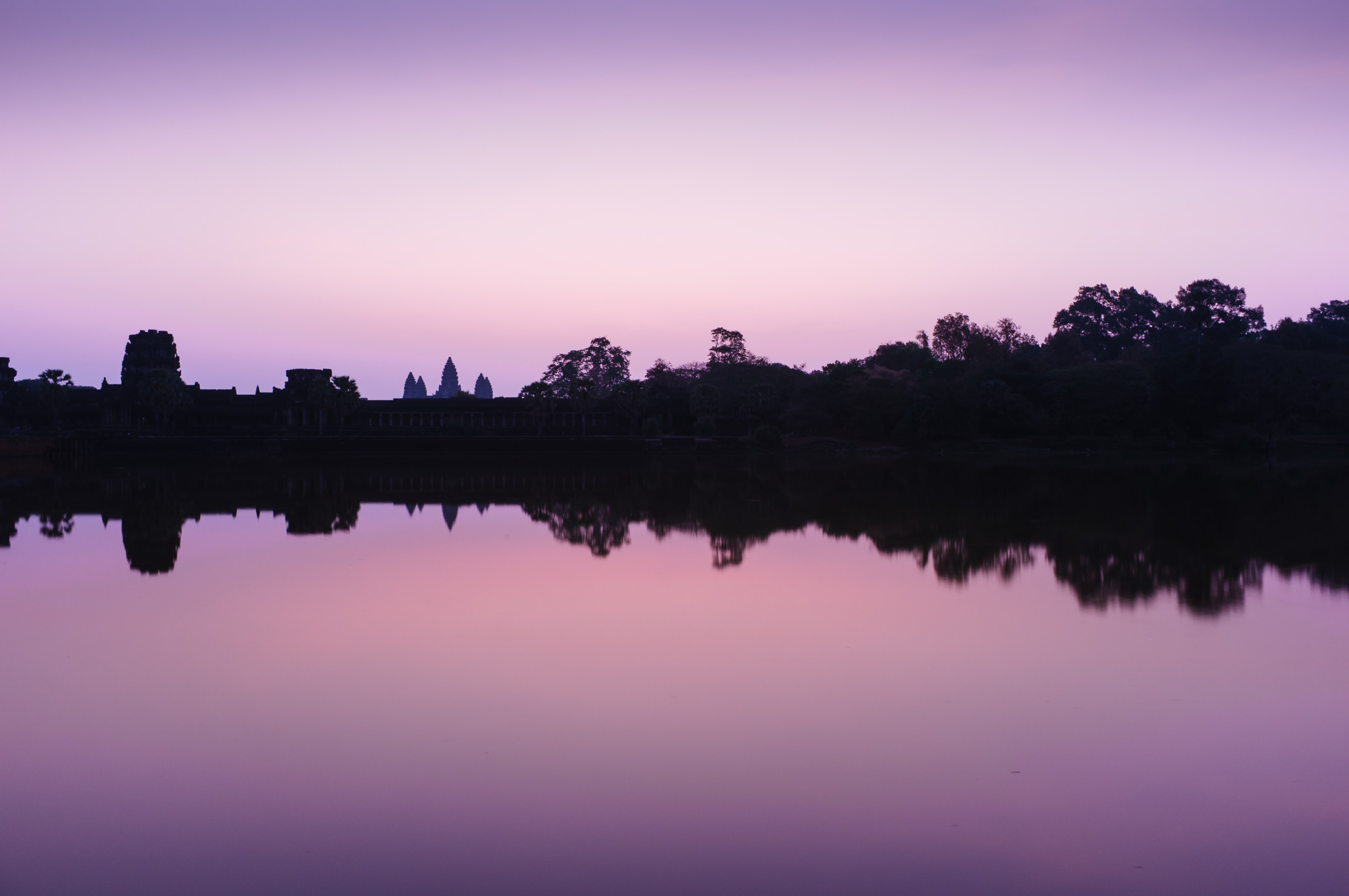 Lake shoreline is reflected in still water during a purple sunset at dusk.