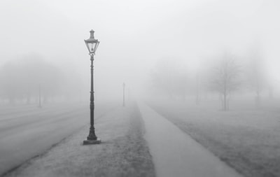 grayscale photo of street post with smoke fog zoom background