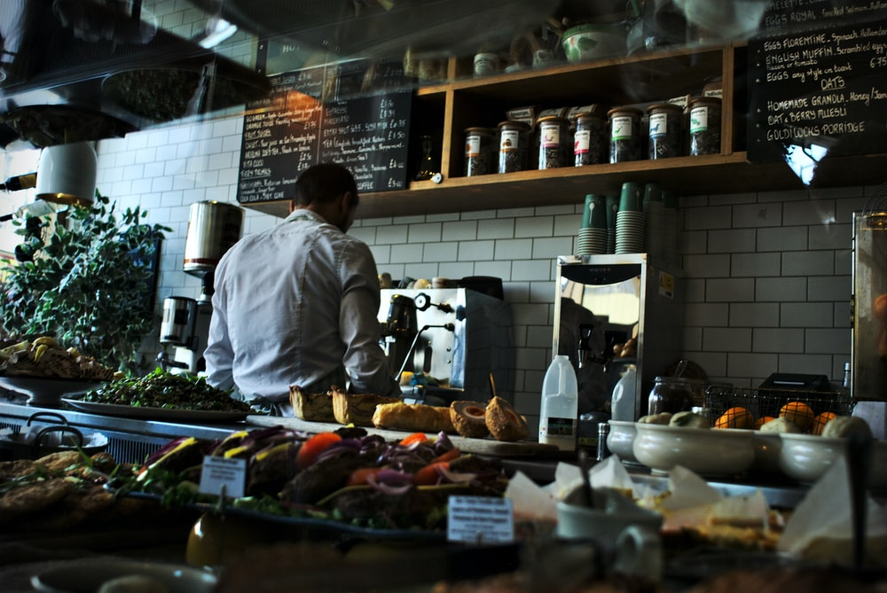 A cook working behind a counter in a café